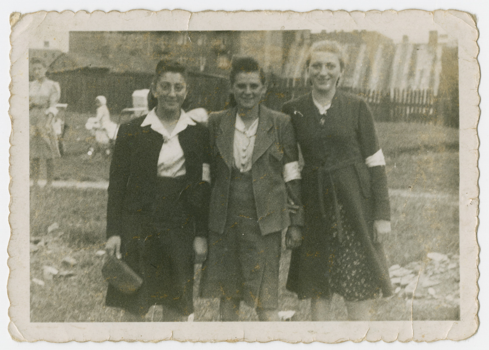 Three young women wearing armbands pose outside in the Sosnowiec ghetto.  Genya Rosenzweig (sister of David) is pictured in the center.