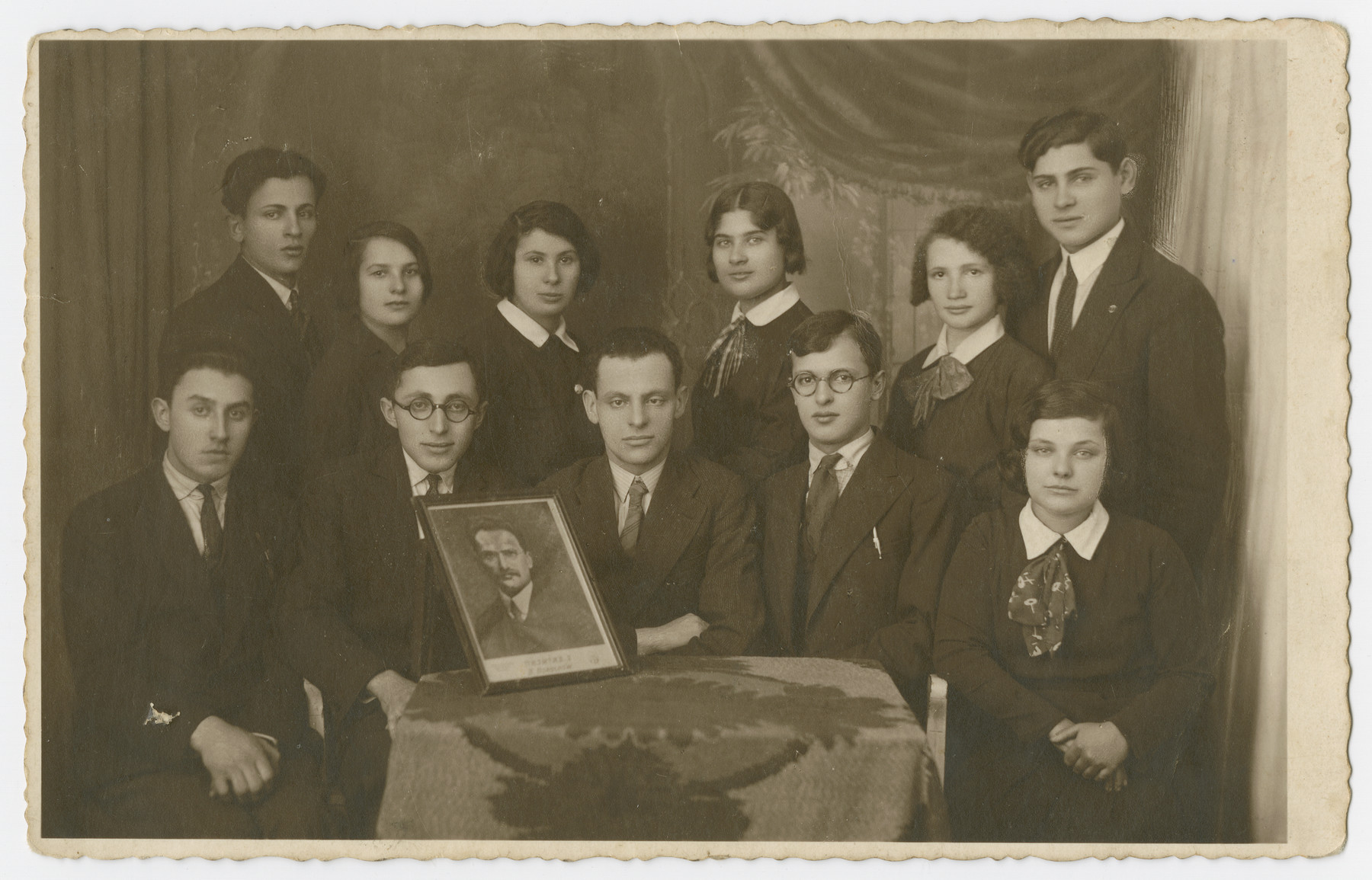 Group portrait of young men and women (possibly members of a youth organization) holding a portrait in prewar Sosnowiec.