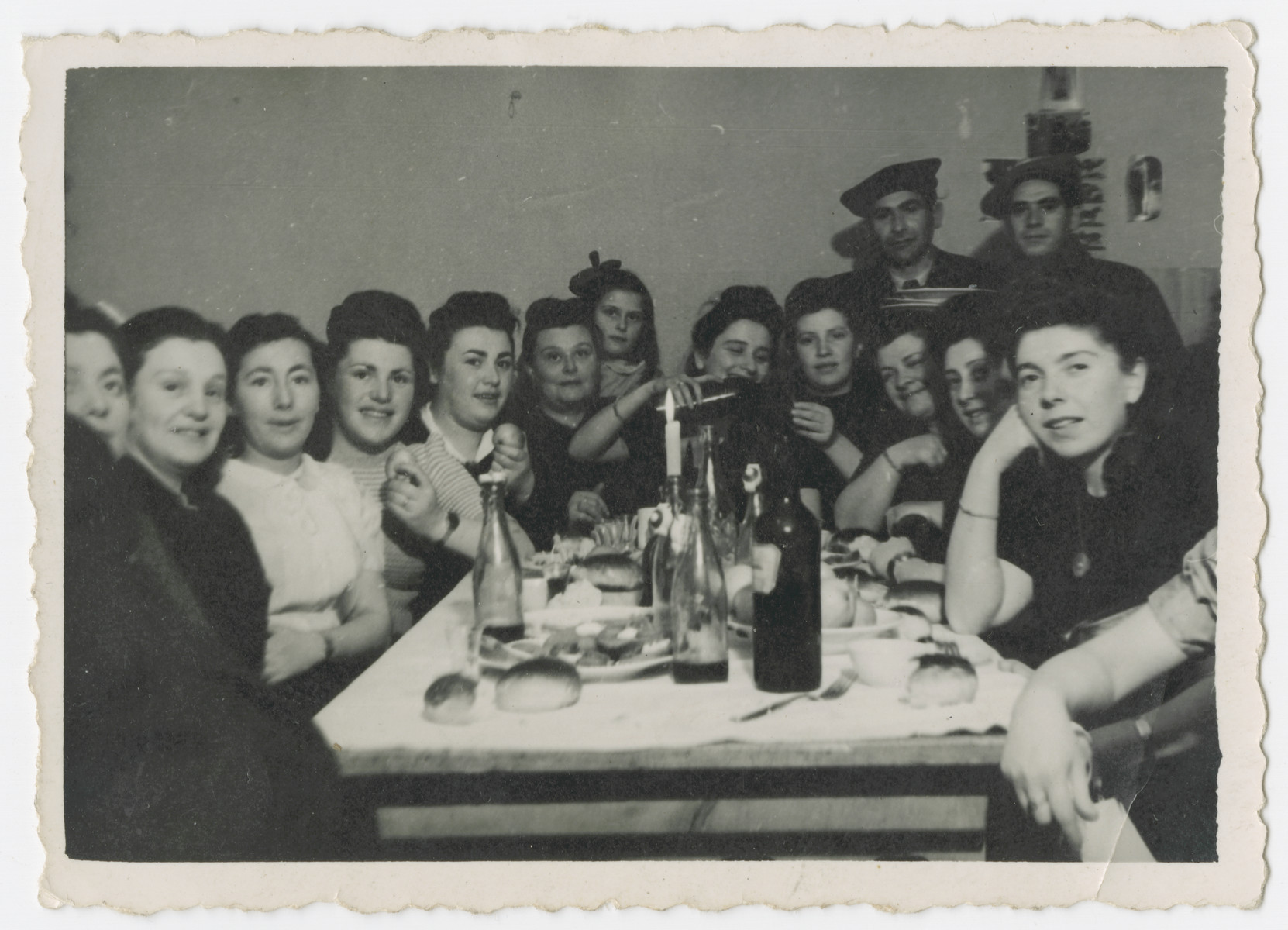 A group of men women gather around a festive table in the Bergen-Belsen displaced persons camp.  David Rosenzweig is pictured in the back.