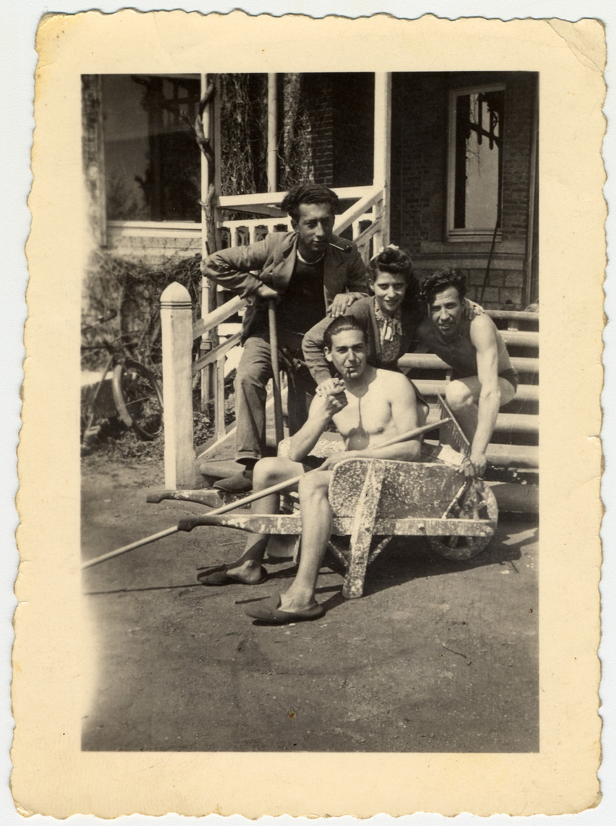 Four Jewish youth relax outside a building in La Ramee agricultural school.  Haim Sephiha is seated in the wheel barrow.  Siggi Daniel leans on a hoe.