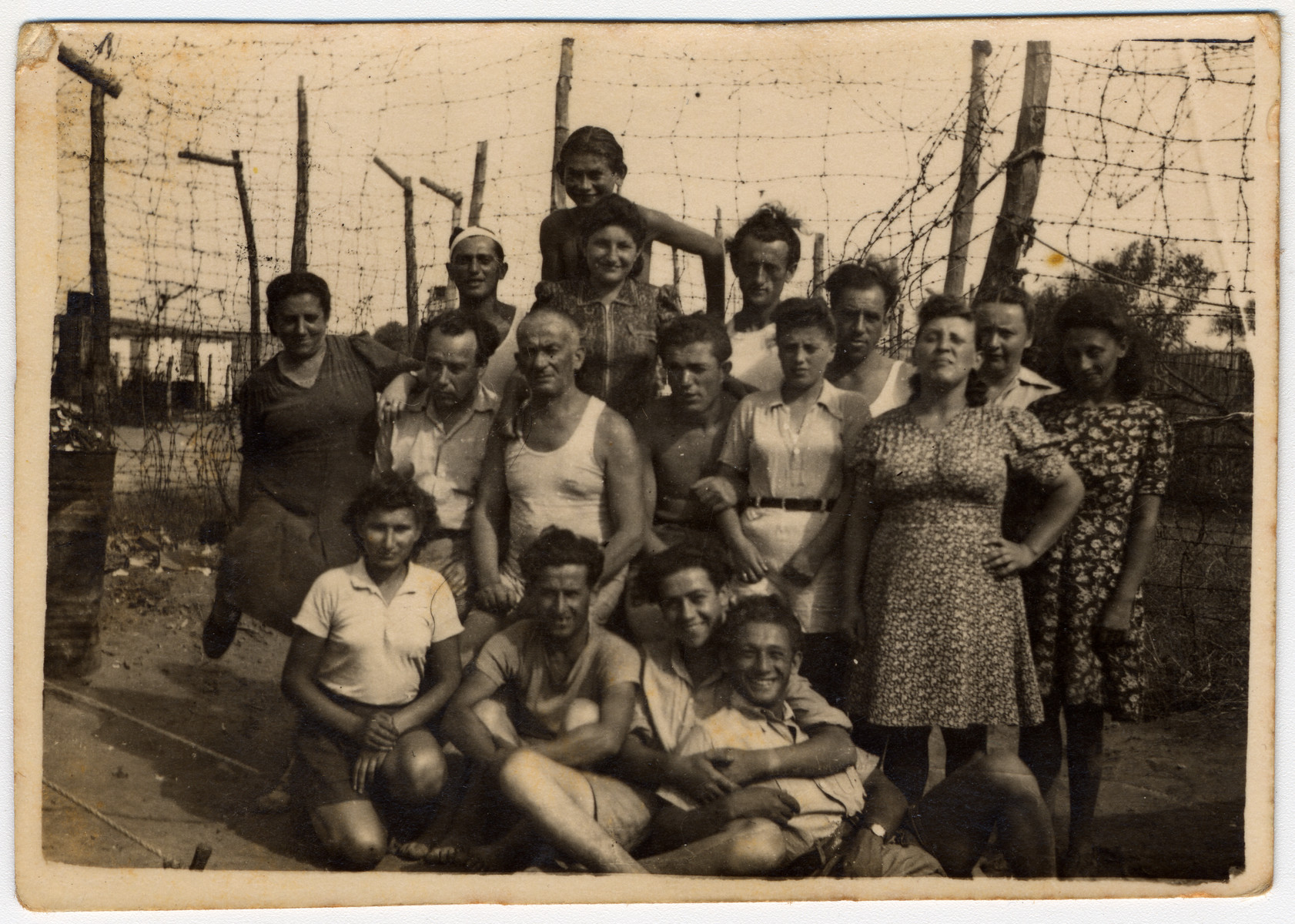 Group portrait of Jewish DPs posing in front of a barbed fence at an internment  camp in Cyprus.