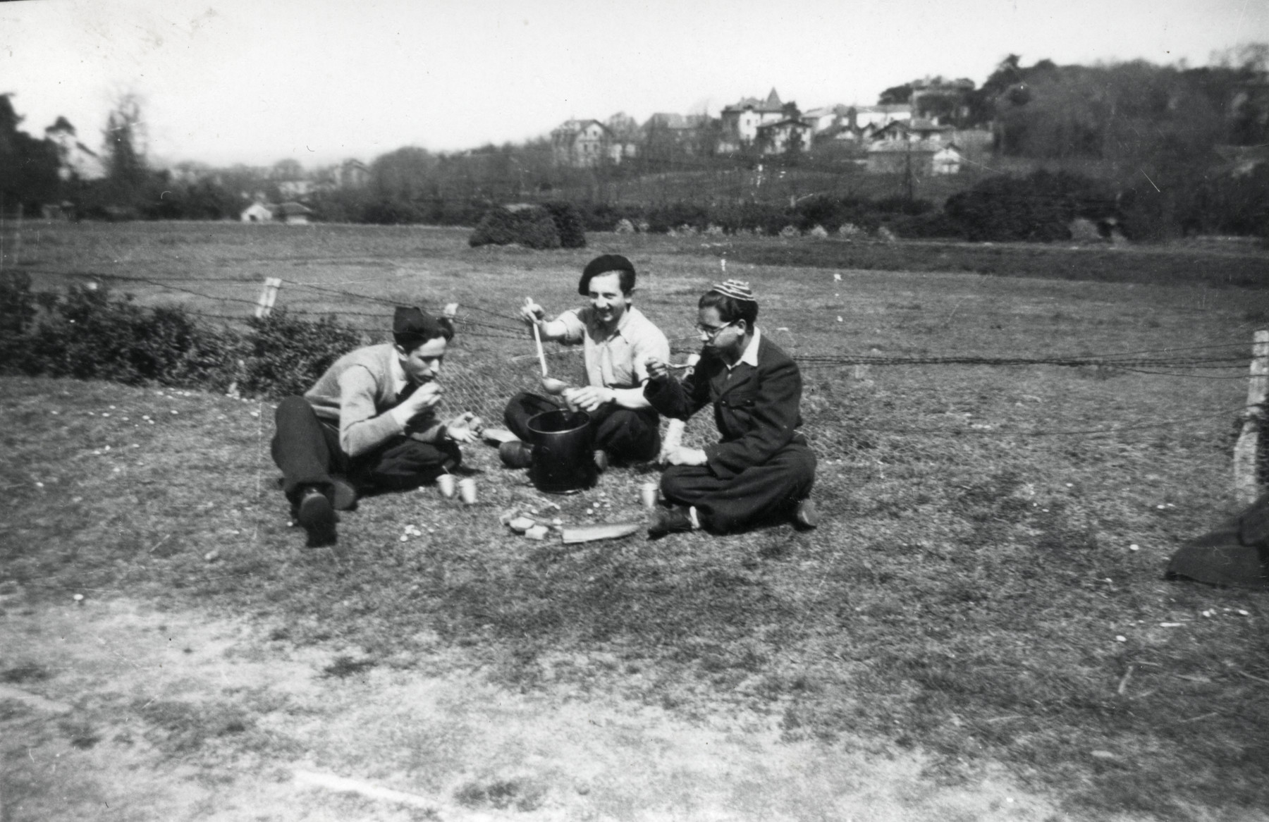 Three teenage boys eat outside during the Passover holiday.  Binem Wrzonski is pictured in the center.