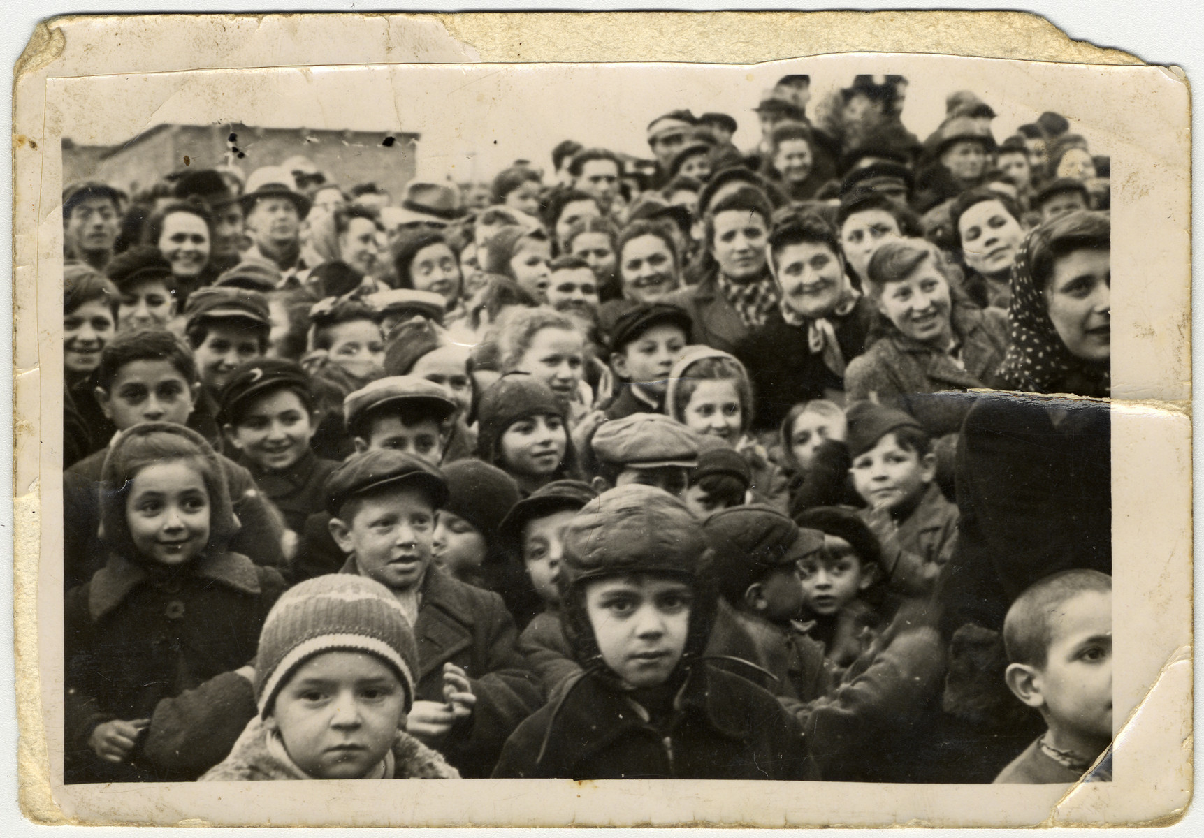 A large group of children and adults crowds together in the Zeilsheim displaced persons' camp.  Henik Minuskin is at the bottom, wearing a Russian pilot's hat.