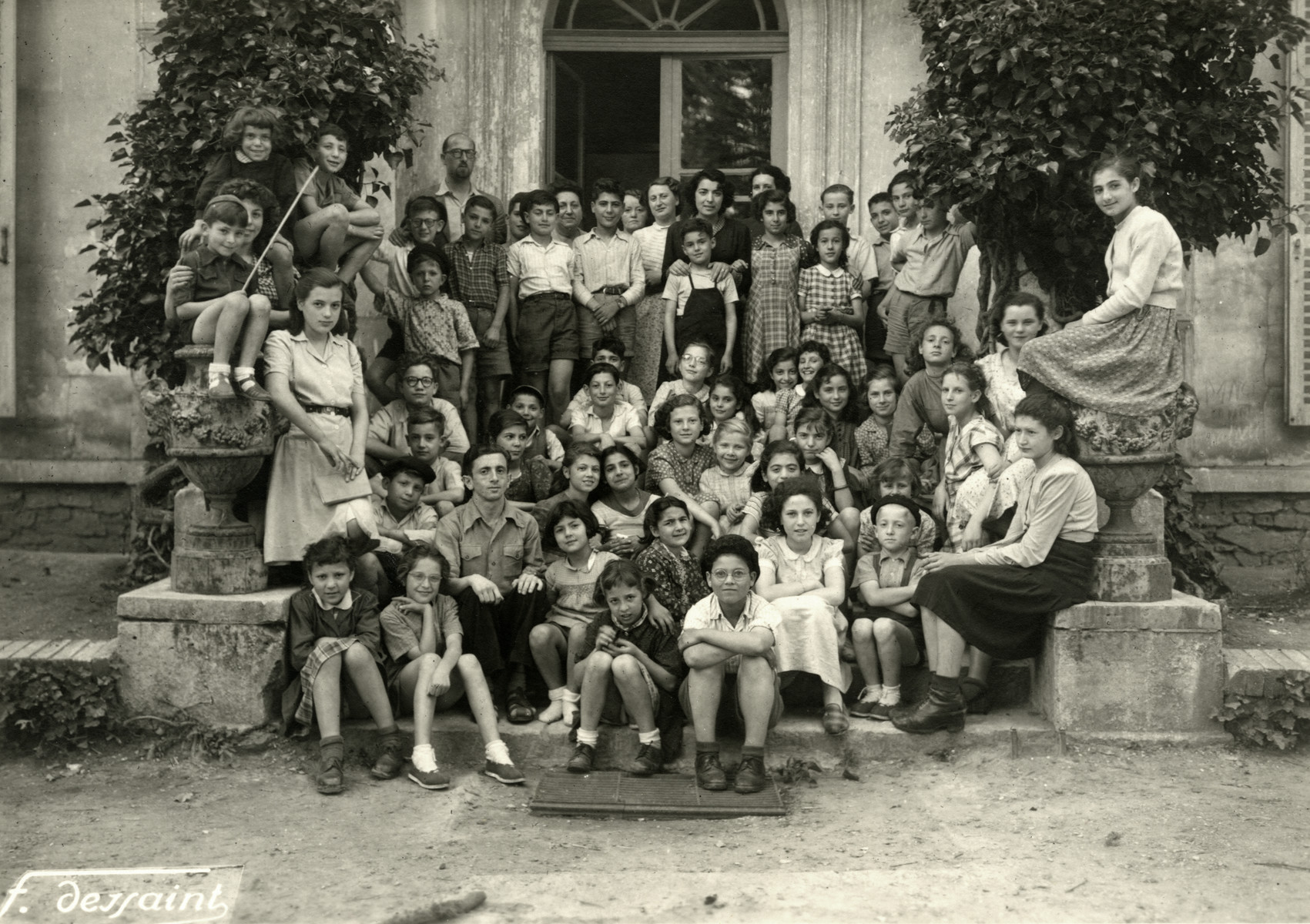 Children and staff of the OSE children's home in Taverny.  Binem Wrzonski who is working as a counselor is pictured on the bottom, third from the left.  Mr. Erich Hausmann, another counselor, is standing in the back row.  Helene Ekayser Weksler, a girl's counselor is on the left with her arm around a little boy.  Among the children is Felice Zimmern (wearing glasses, center), her sister Beatte (two rows in front to her right), Gisele and Lise Behar (above her) and Leon Bretmel (first person standing on the steps, on the left).