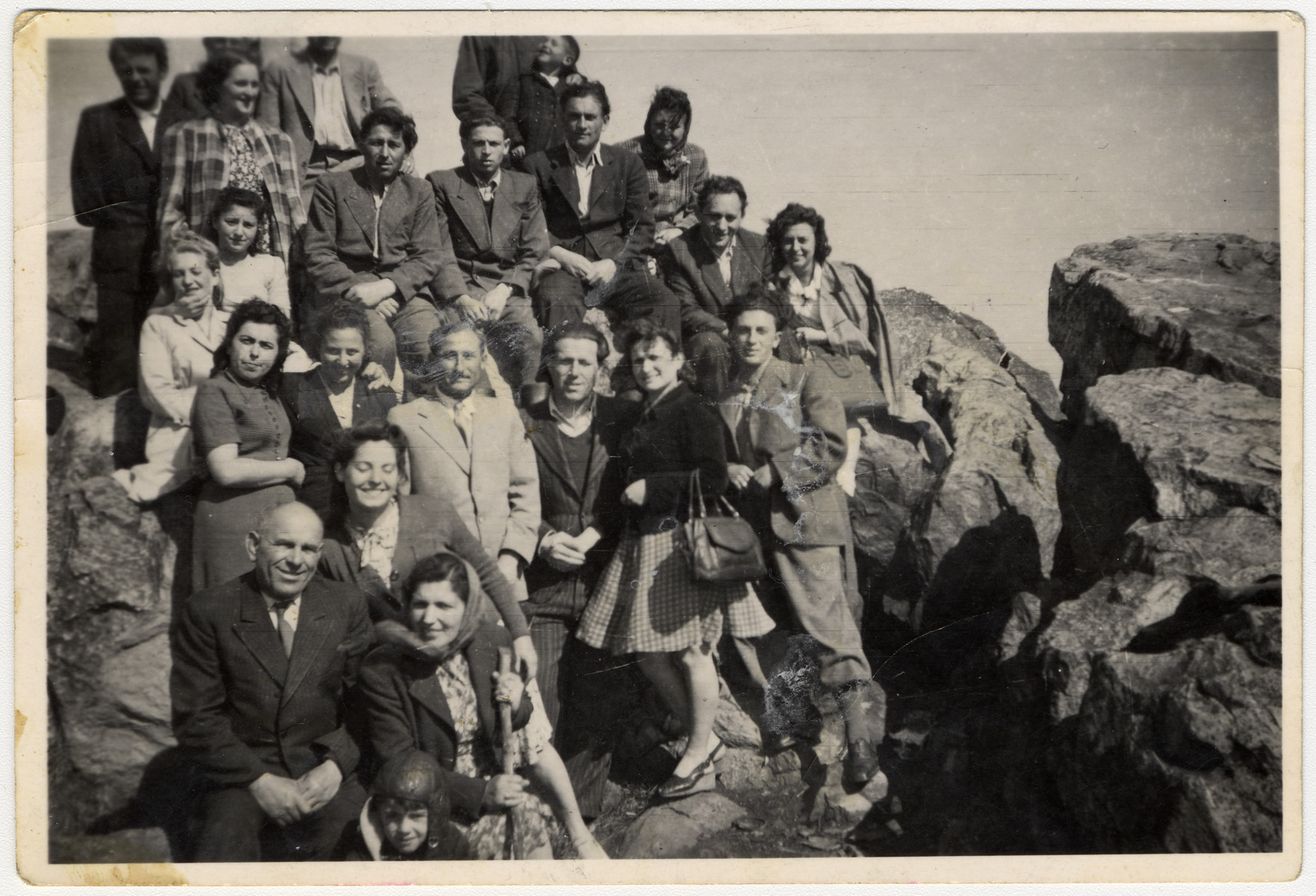 A large group of Jewish displaced persons goes on an excursion in the rocky countryside near Frankfurt.  Among those pictured (on the bottom) are Misha Mendel Lazarovitch (left), Channa Bienavoitch and Shanke Minuskin.