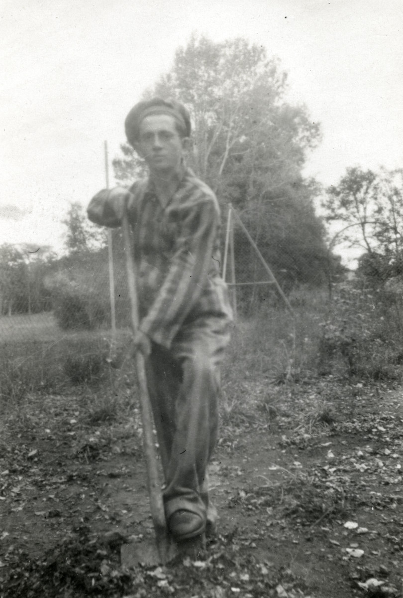 Binem Wrzonski digs in the garden of the Ambloy children's home while wearing an old concentration camp uniform.