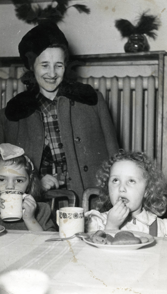 A woman stands next to two toddlers who are eating a meal in an unidentified children's home [perhaps Chez Nous].