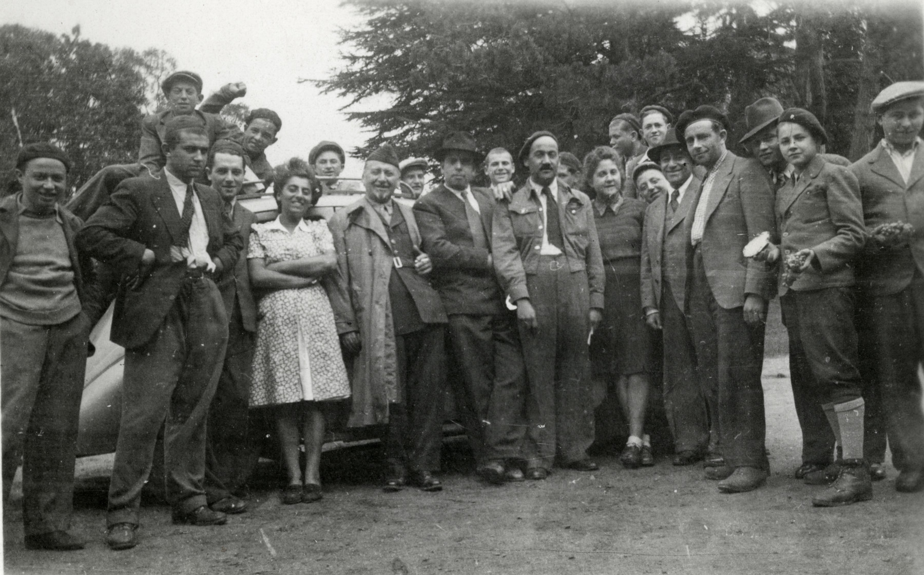 Staff and teenagers pose on the grounds of the Ambloy children's homes during the visit of a British chaplain who was the brother of one of the boys and came to meet him during the Sukkot holiday.  Nina is in front left; Judith Hemmendinger is fouth from the right.  Next to him is Mareplis, the boy who is to meet his brother.  The chaplain is pictured in the center, wearing a beret and short battle jacket.