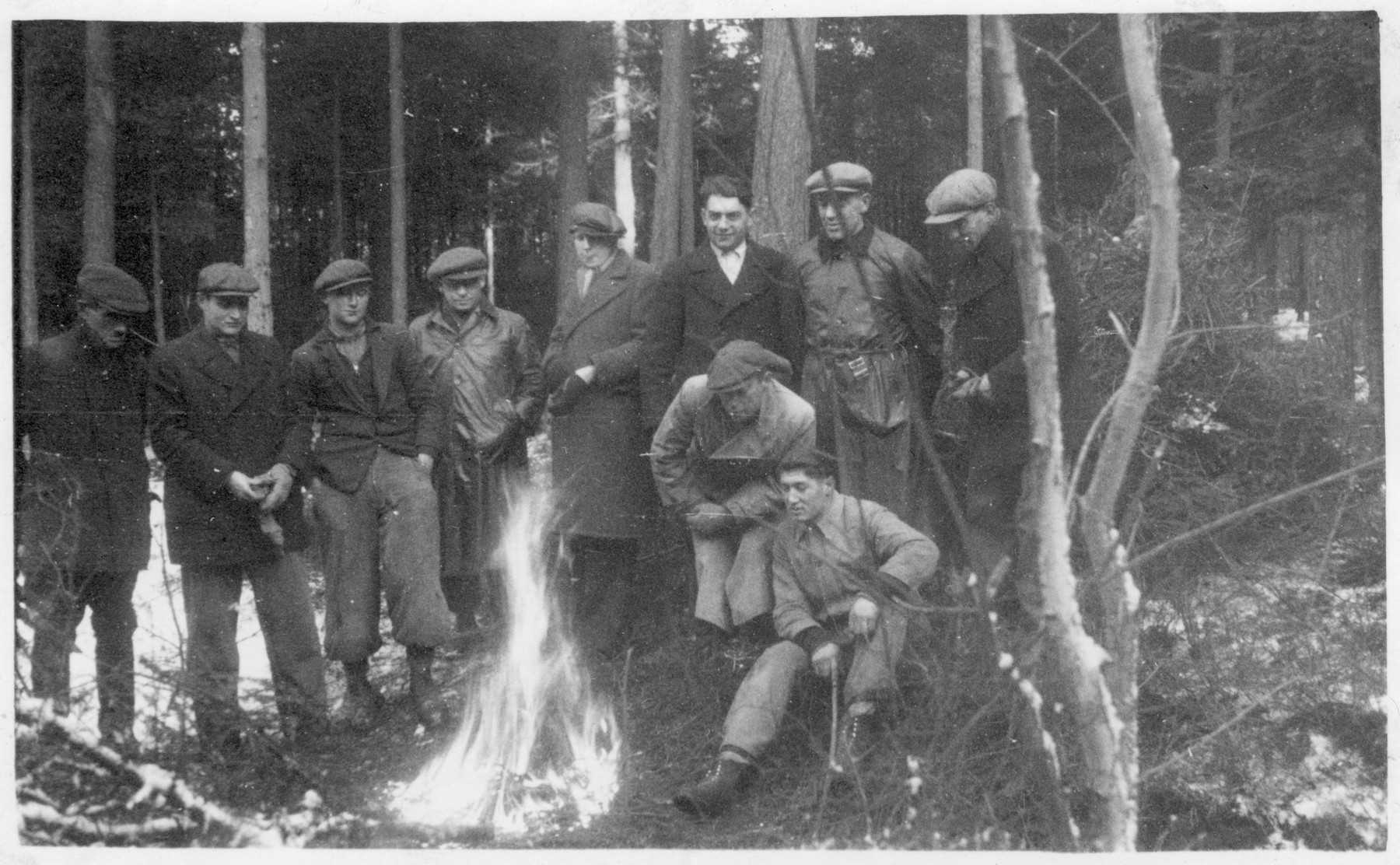 Workers from the Lipa labor camp gather by a fire in the woods.  Among thiem in Vasicek's father.