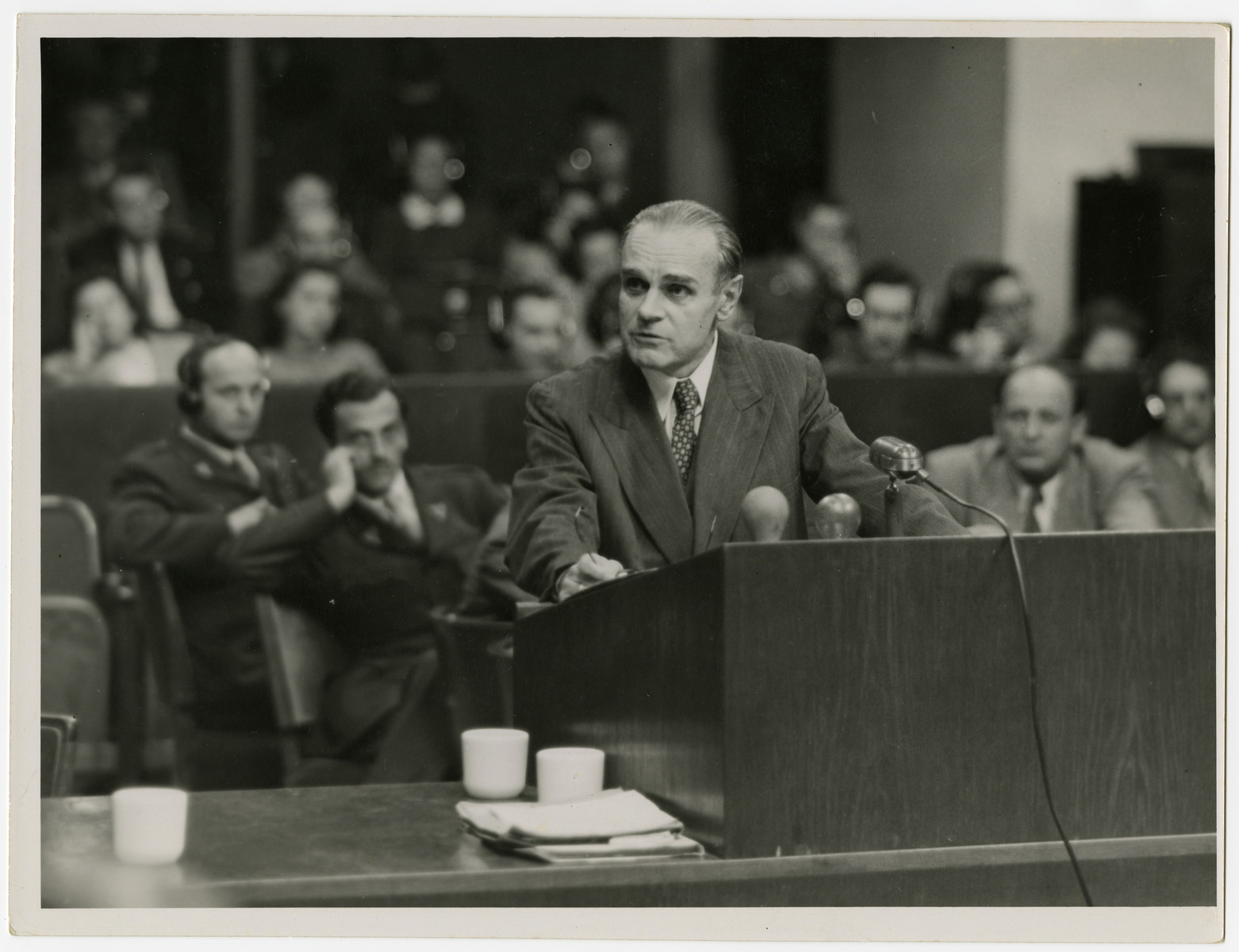 One of the 12 defendants testifies during the Krupp tribunal.  Seated behind him to his right is Max Austein.