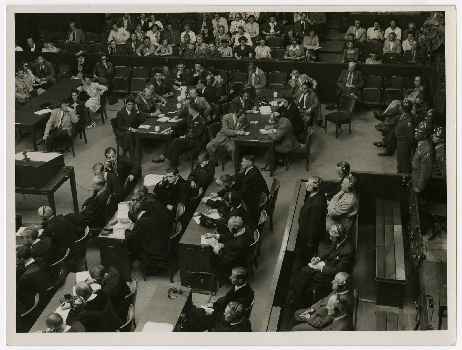 One of the defendants of the Krupp Case stands in the defendants dock while American military police stand behind him.