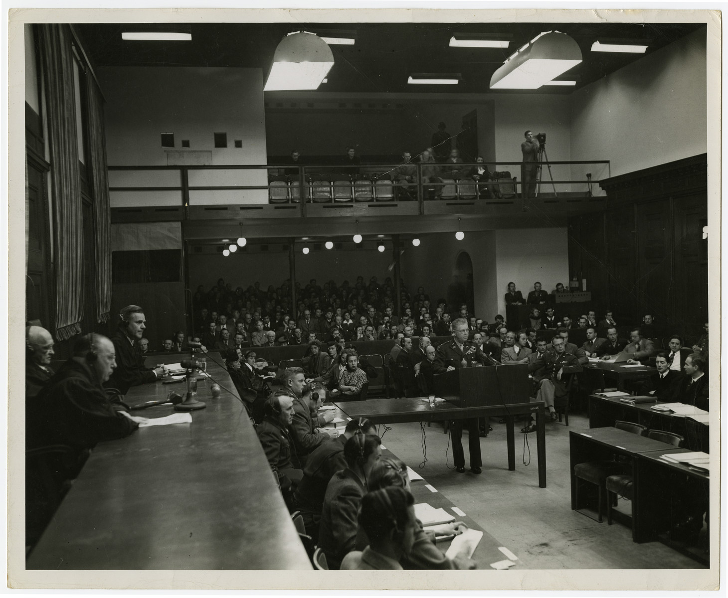 An American prosecutor testifies during the Krupp Tribunal.  The three justices are seated on the left  and Telford Taylor, chief prosecutor, is to the right of the man testifying.