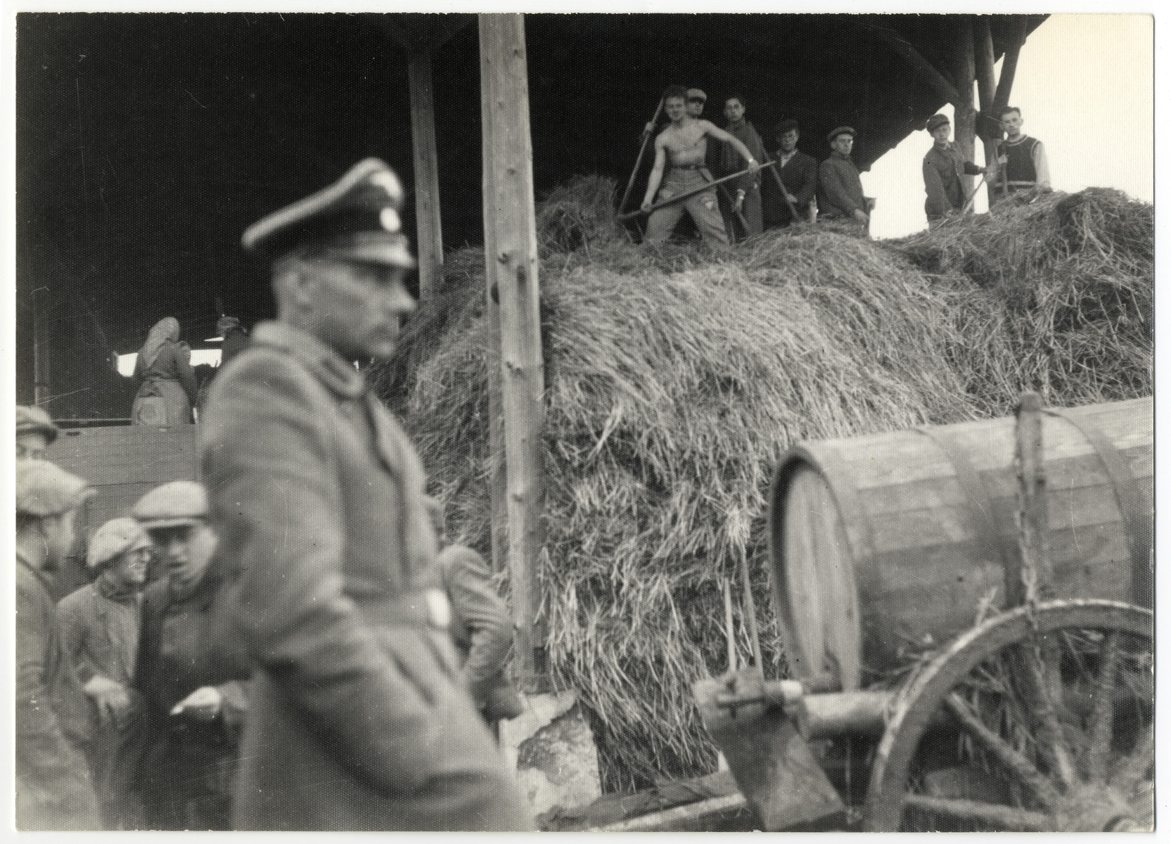 SS guard Schmiller walks past the barn of the Lipa farm labor camp where Jewish workers are pitching hay.
