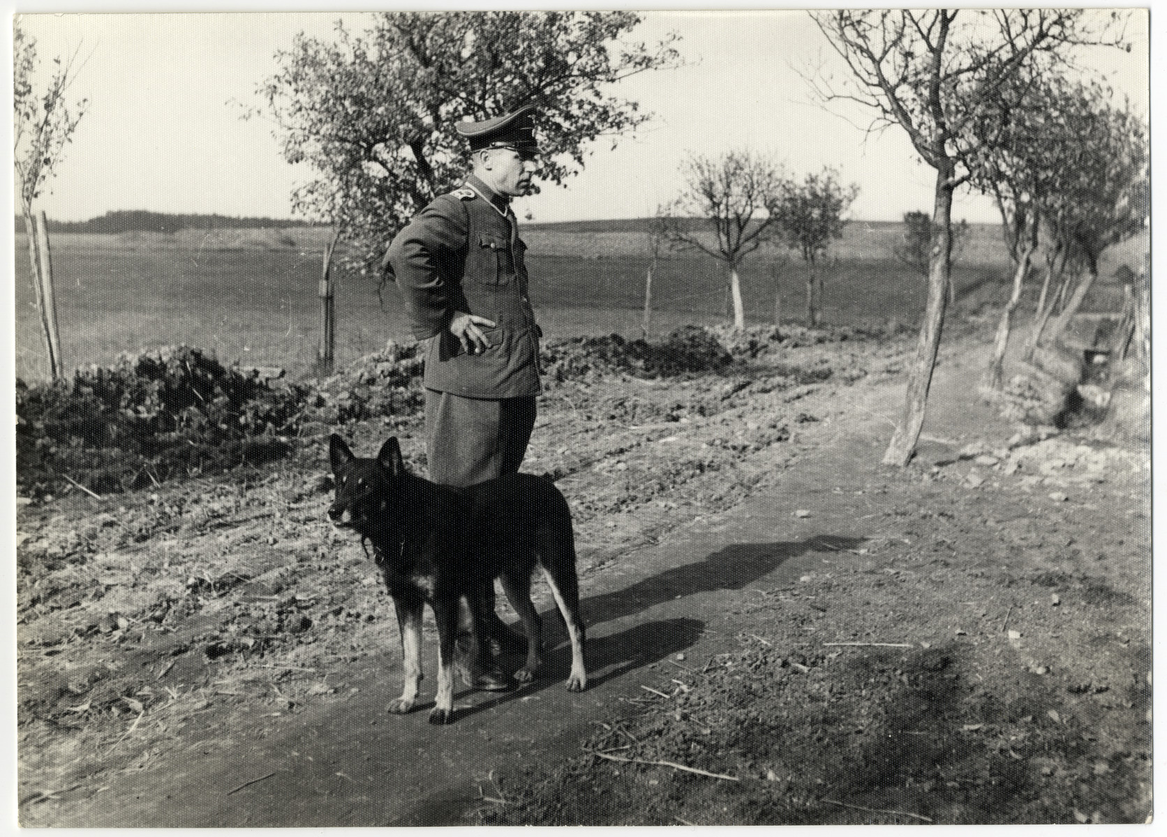 SS guard Schmiller stands on a dirt road in the Lipa farm labor camp with his dog.