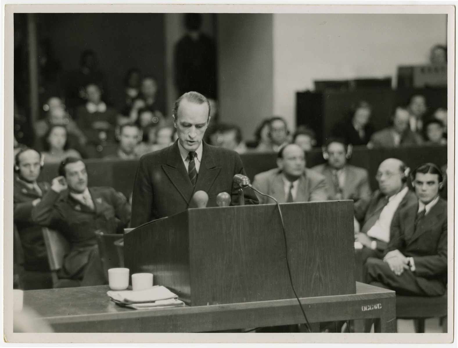 Defendant Alfred Krupp von Bohlen testifies at the Krupp Case war crimes trial.  Seated behind him to his right is Max Austein.