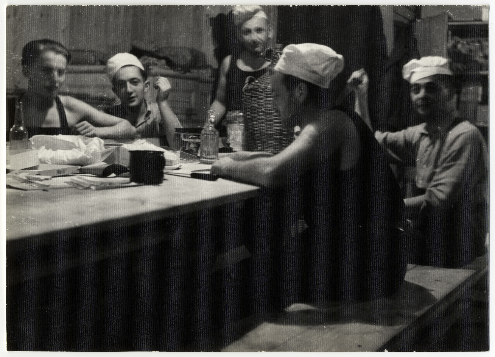 Workers sit  by a table in the kitchen of the Lipa farm labor camp.