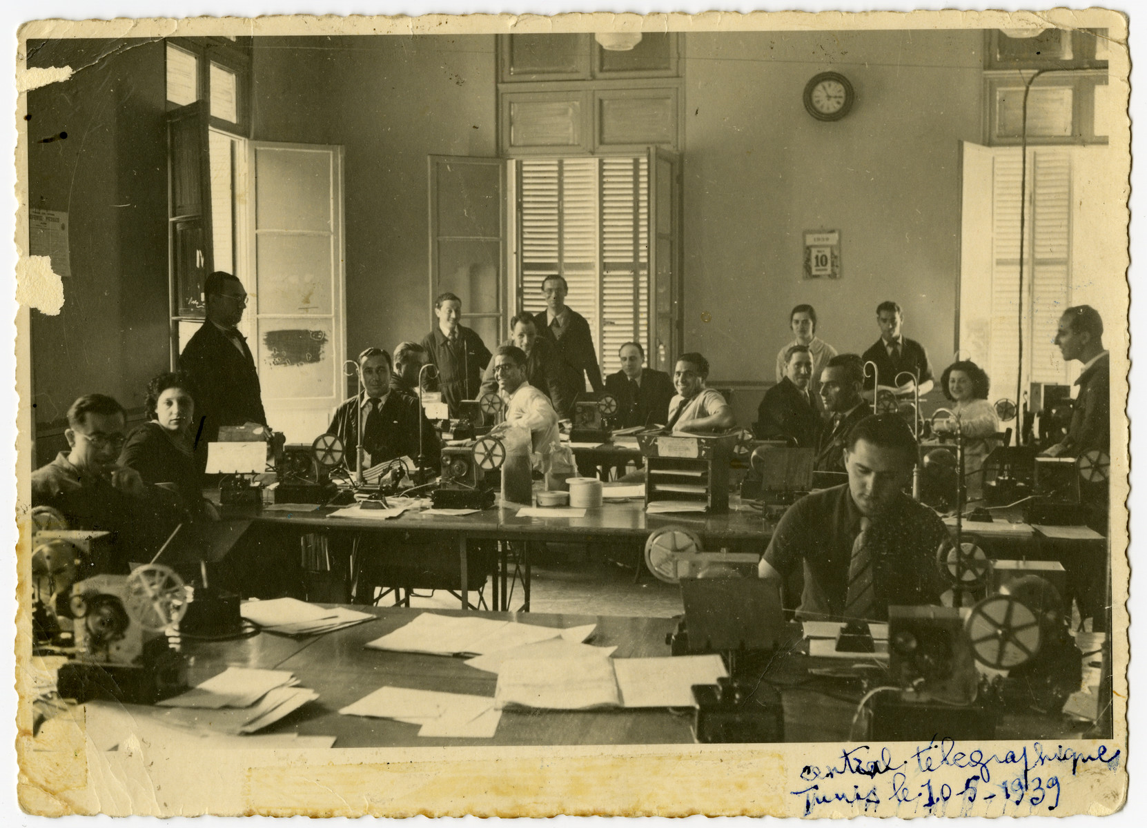 Workers of the Central Telegraph Office in Tunis operate their teletypes.  Arlette El Haik (later Benichou) is pictured near the window on the right.  Also pictured are Bost, Clance, Florane, Mlle Allouche, Capot, Taieb, Costa, Vitalis, Ousedere and Canavaggio.