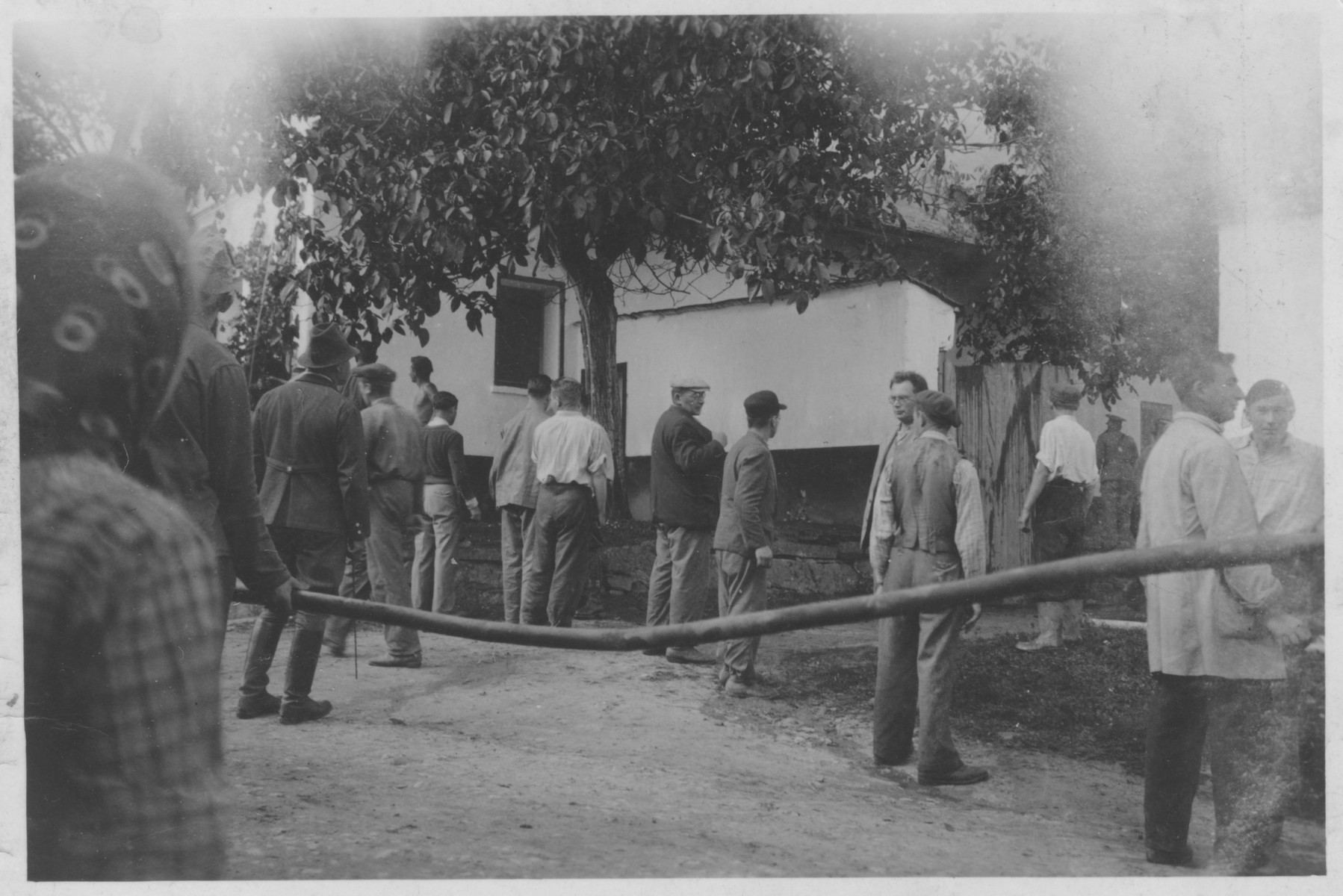Boellmann (third from the left), the first chief of the Lipa camp, oversees Jewish workers extinguishing a fire.