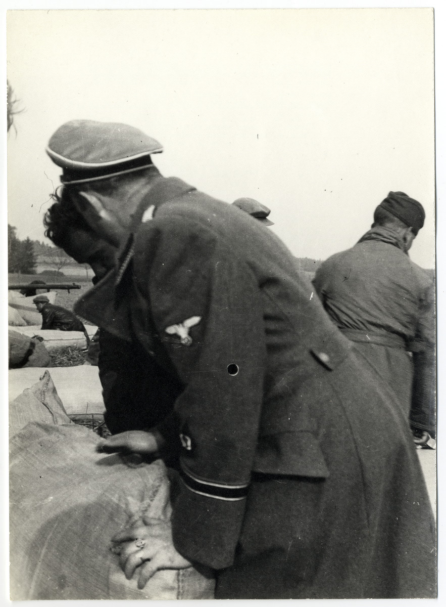 An SS guard [possibly Schmiller] supervises work in the Lipa farm labor camp.