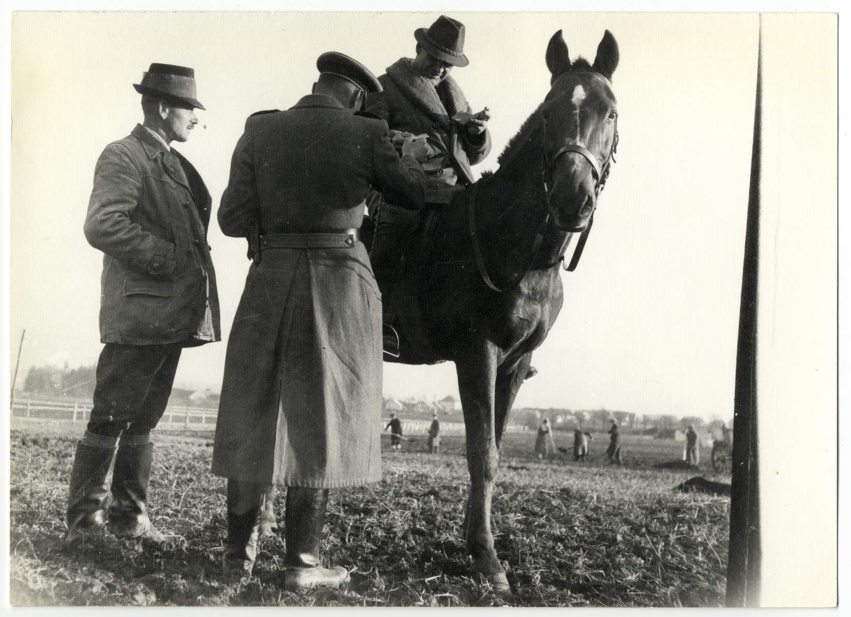 Three administrators of the Lipa farming labor camp confer with each other while slave laborers work in the background.  From left to right are a Czech farm administrator, SS guard Schmiller, and chief farm administrator and NSDAP member Karel Fousek (on the horse).