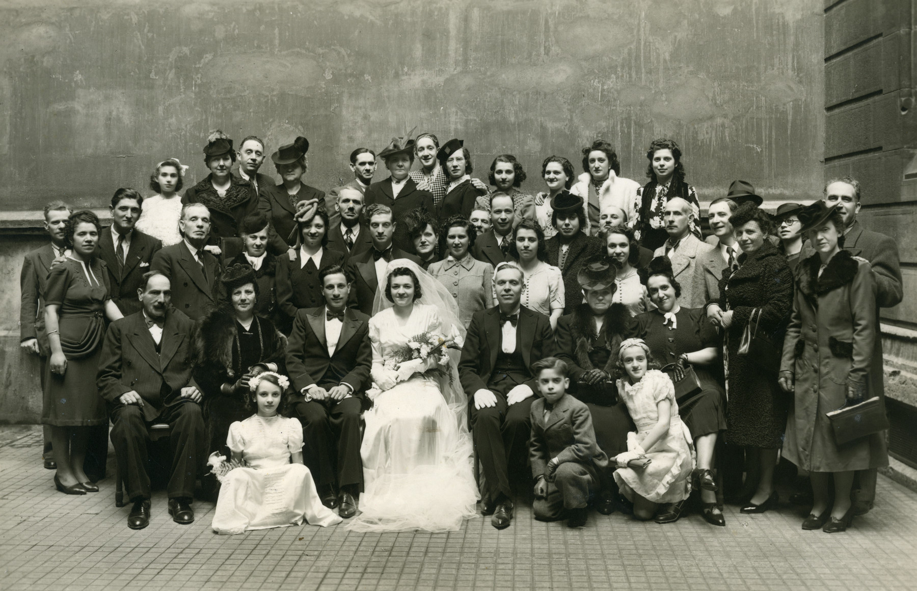 Wedding portrait of Rachelle Romano and Yom Tov Chavez.  Pictured in the center isthe bride Rachelle Romano next to her father Shimon Romano. His wife Regine Romano is to his right.  Camille Romano is seated in a white dress on the left.  Standing to the left of Shimon are his daughters Esther and Julliette.  Another sister Suzanne is standing in the back row, fourth from the right.  Joef Emir is in the back row center.
