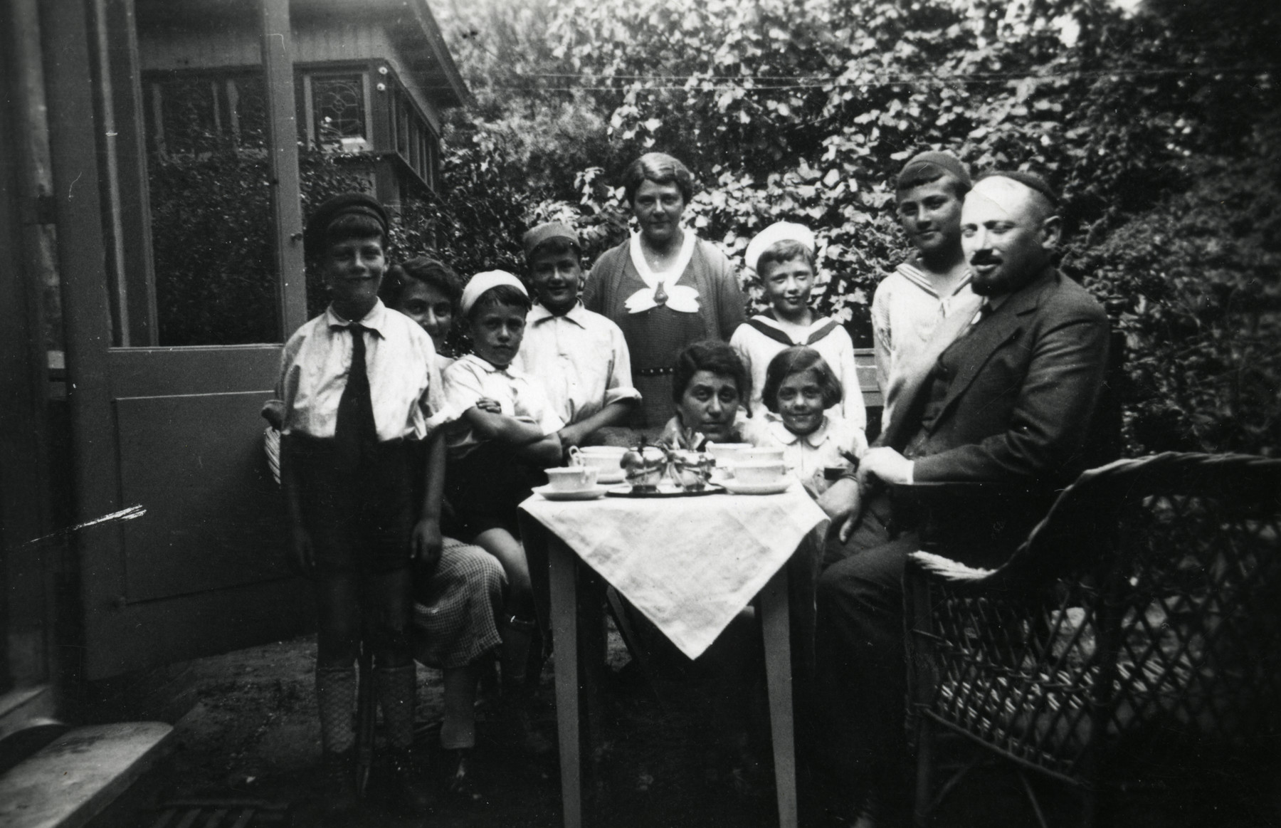 Chana and Mordechai Emanuel stand with their children by a table outside their home.
