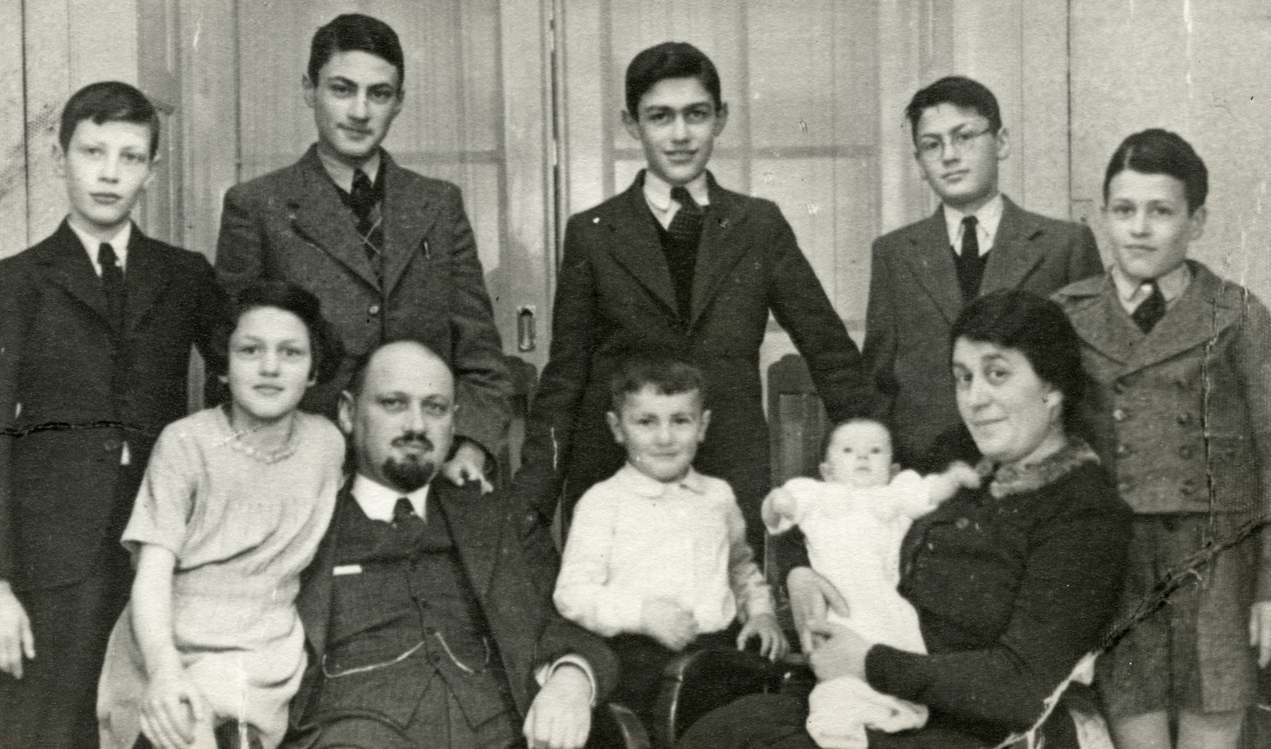 The Emanuel family gathers for  a family portrait the preceding Shmuel's bar mitzvah.    Standing from right to left:  Baruch, Yona, Shlomo, Elchanan, and Shmuel.  Sitting:  Chana holding Bitya, Shalom, Mordechai, and Bella.
