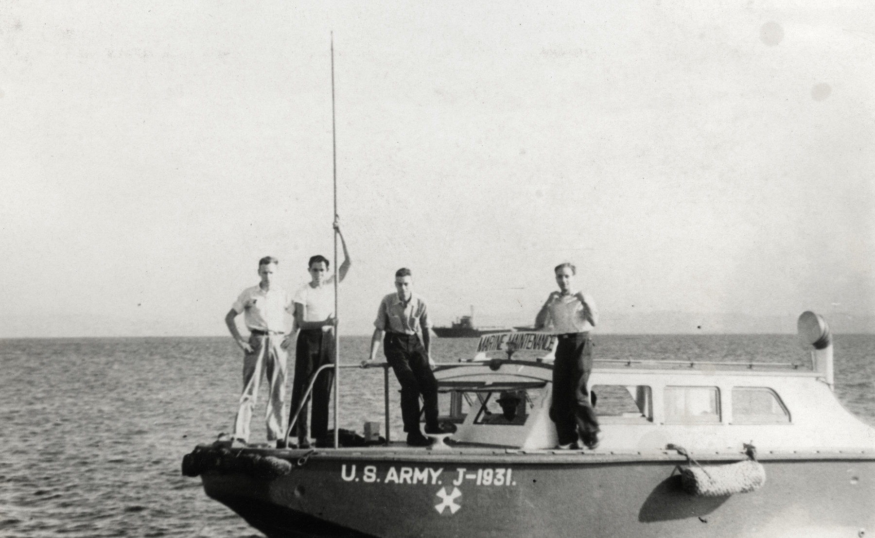 Kurt Markus poses with his friends Slutzky, Julian Burt, and Eddie Alcock on a boat while working for the American navy.