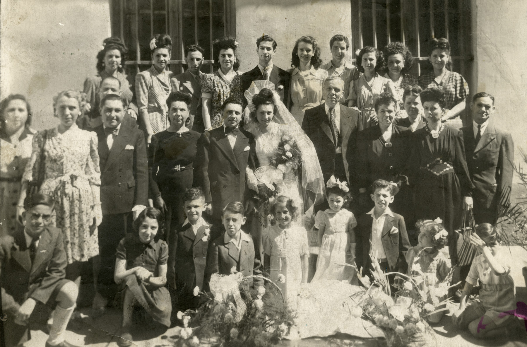 Wedding portraitof Suzanne Romano and Jacques (Jaakov) Levy.  Shimon and Regine Romano are to the right of the bride.  The groom's mother (a widow) is standing next to him.  Pictured standing in the center are Leon Levi (a cousin) and the donor, Camille Romano.