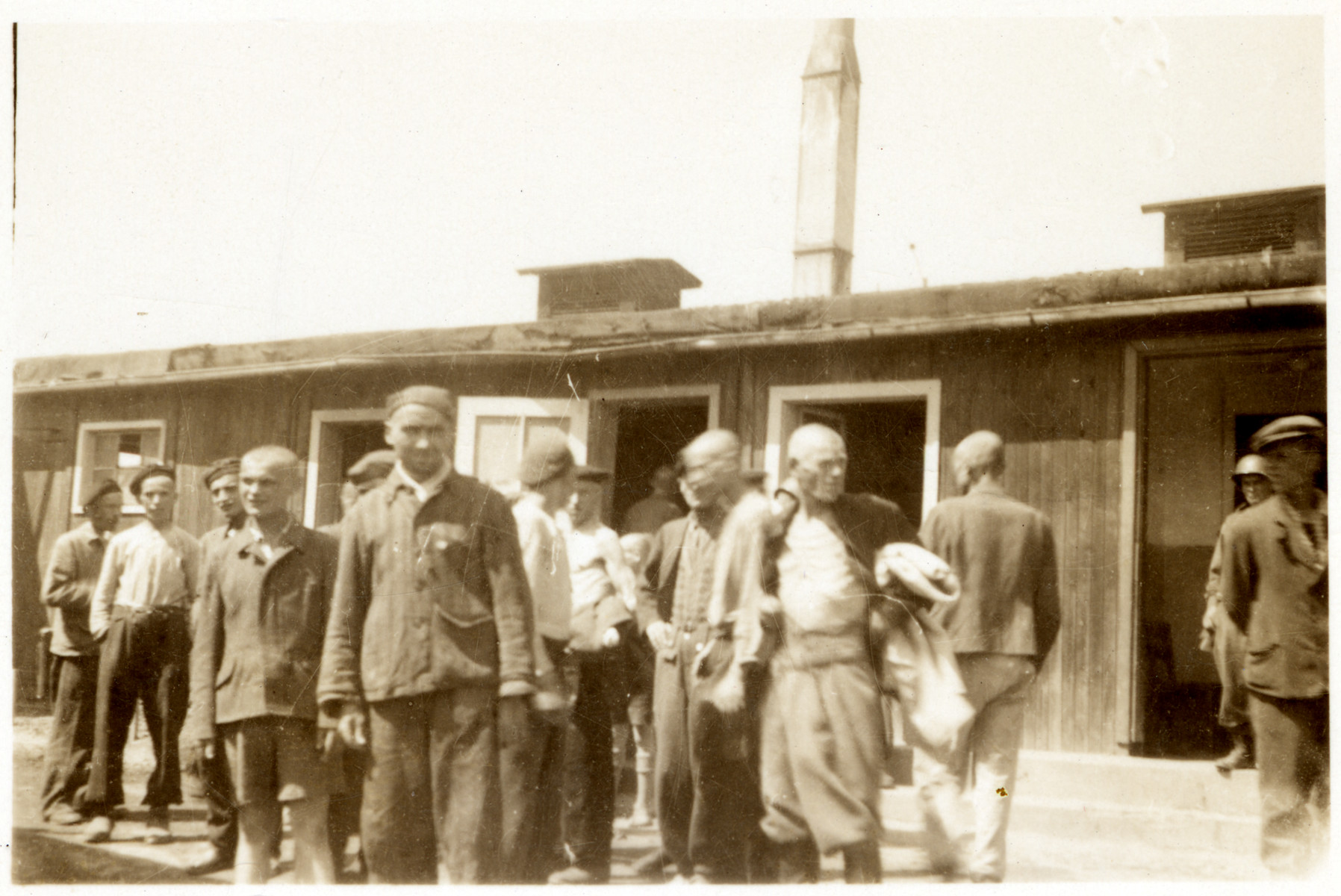 Group portrait of survivors of the Gusen concentration camp standing in front of a barracks.  Standing third from left may be Rubin Szpitalnik who was born Warsaw. and deported to Auschwitz from Paris.