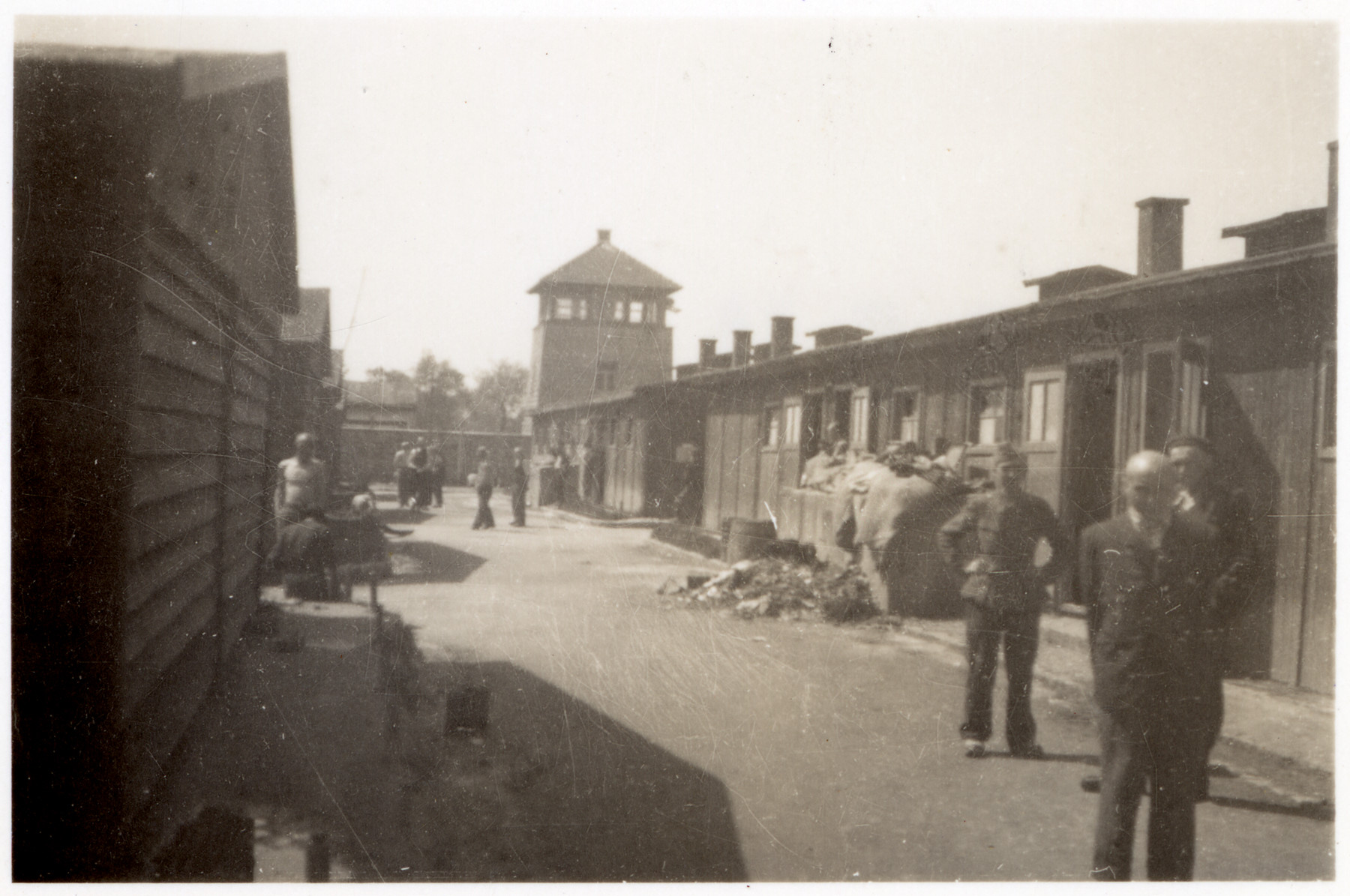 Survivors and American servicemen stand on a main artery of the Gusen concentration camp following liberation.  A watch tower is in the background.