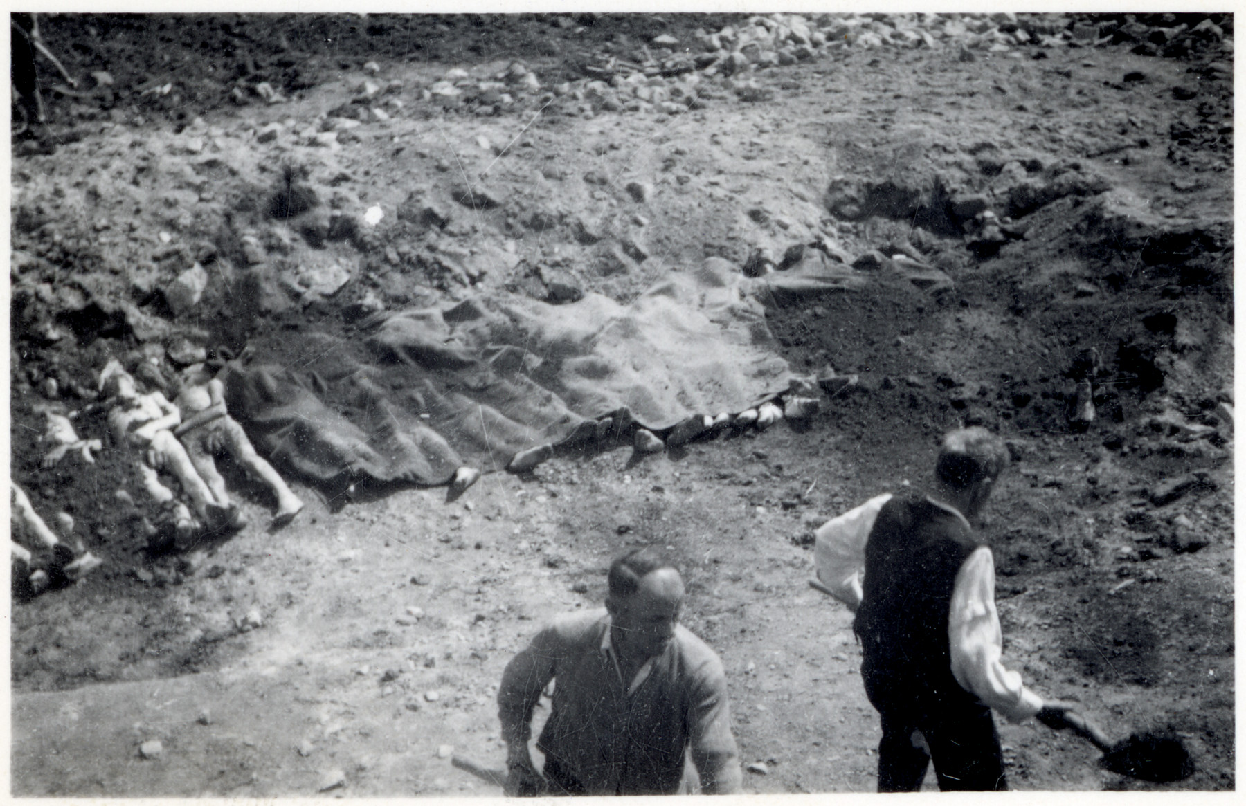 Austrian civilians are forced to bury the corpses of deceased prisoners in the Gusen concentration camp.