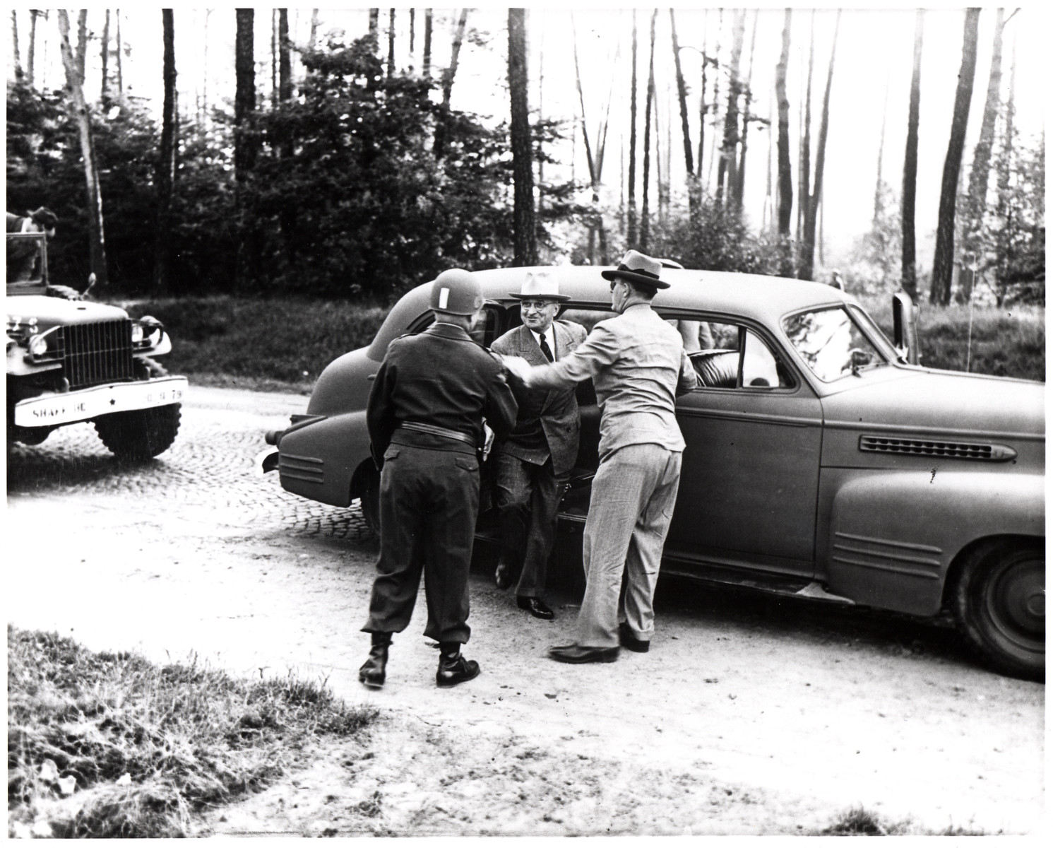 President Harry Trumman exits an automobile to meet with an army officer [perhaps during his visit to Germany to attend the Potsdam Conference].