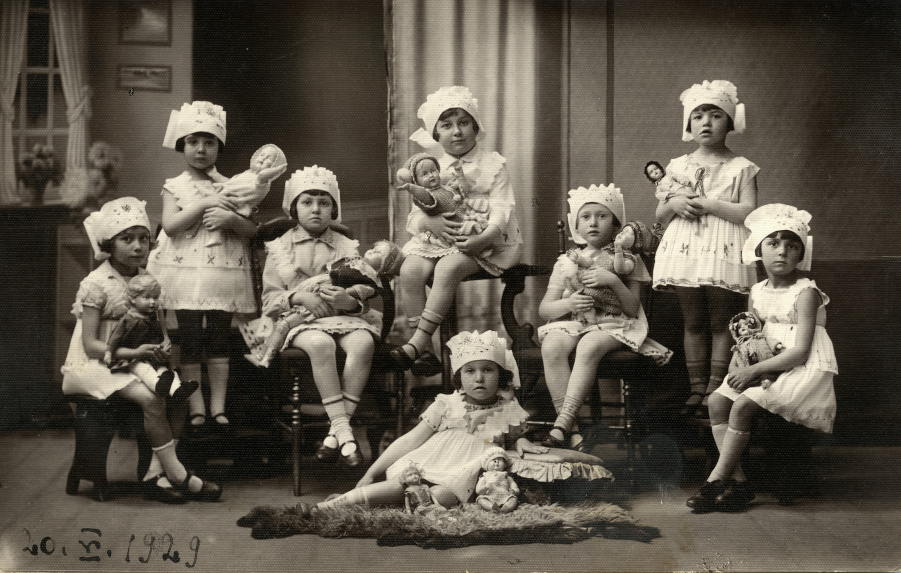 Studio portrait of kindergarten girls holding their dolls and wearing matching bonnets.  Ewa Krakowska is seated third from the right.