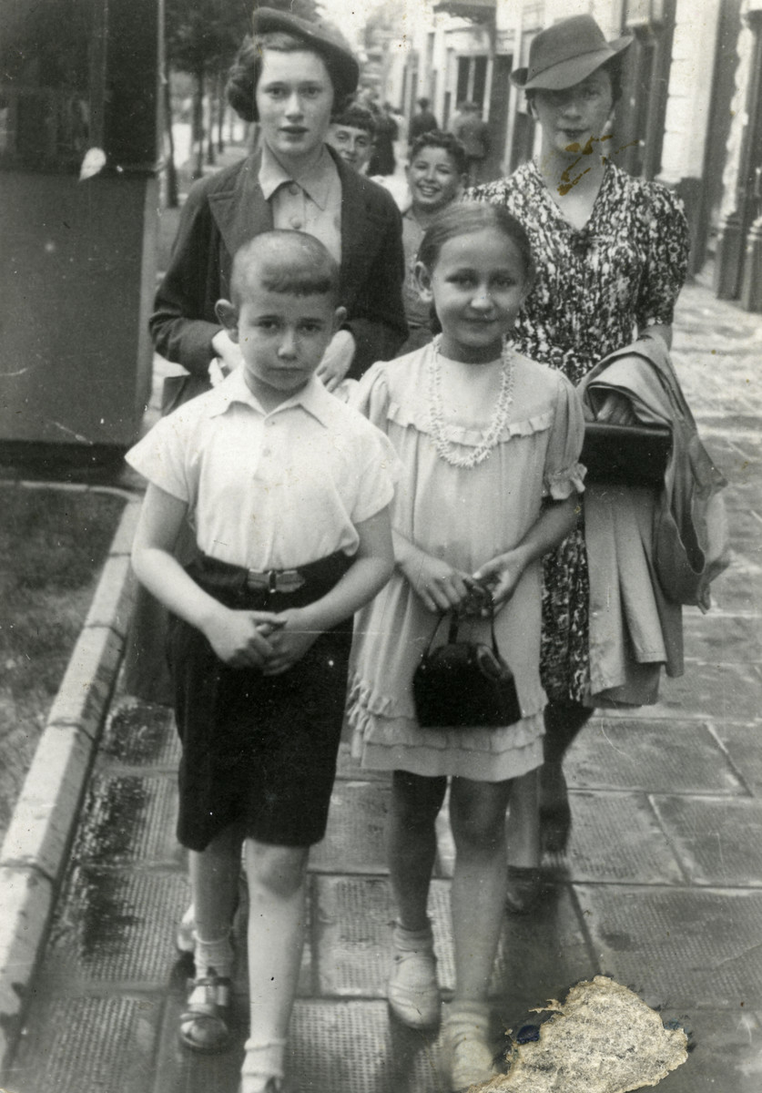 A Jewish family walks down a street in Bialystok.  In back are Eva Krakowska and her cousin Judith.  In front of them are Julik Krakowska and Judith's daughter.
