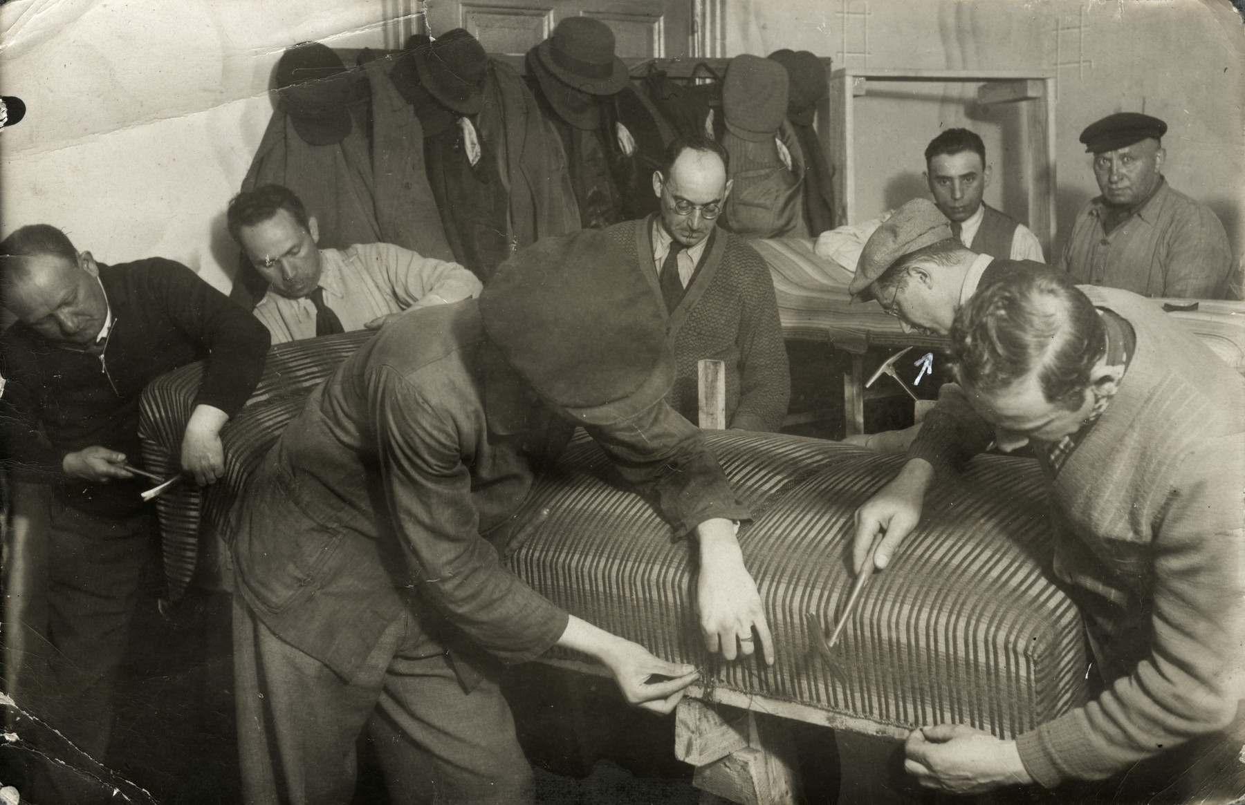 German Jews exiled to Zbaszyn reupholster furniture in a workshop.  Yehoshua Birnbaum is on the middle left with a cap and glasses.