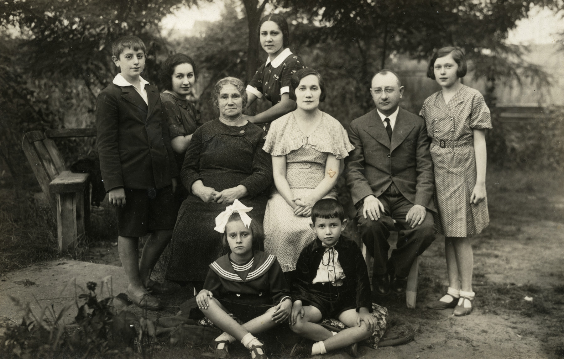 Group portrait of the extended Krakowska family at their summer dacha.  Ewa Krakowska's parents are in the middle, Ewa is standing to the  right of her father, and her brother Julik is seated in front., right.  Berl Rabinovitch is standing on the left.