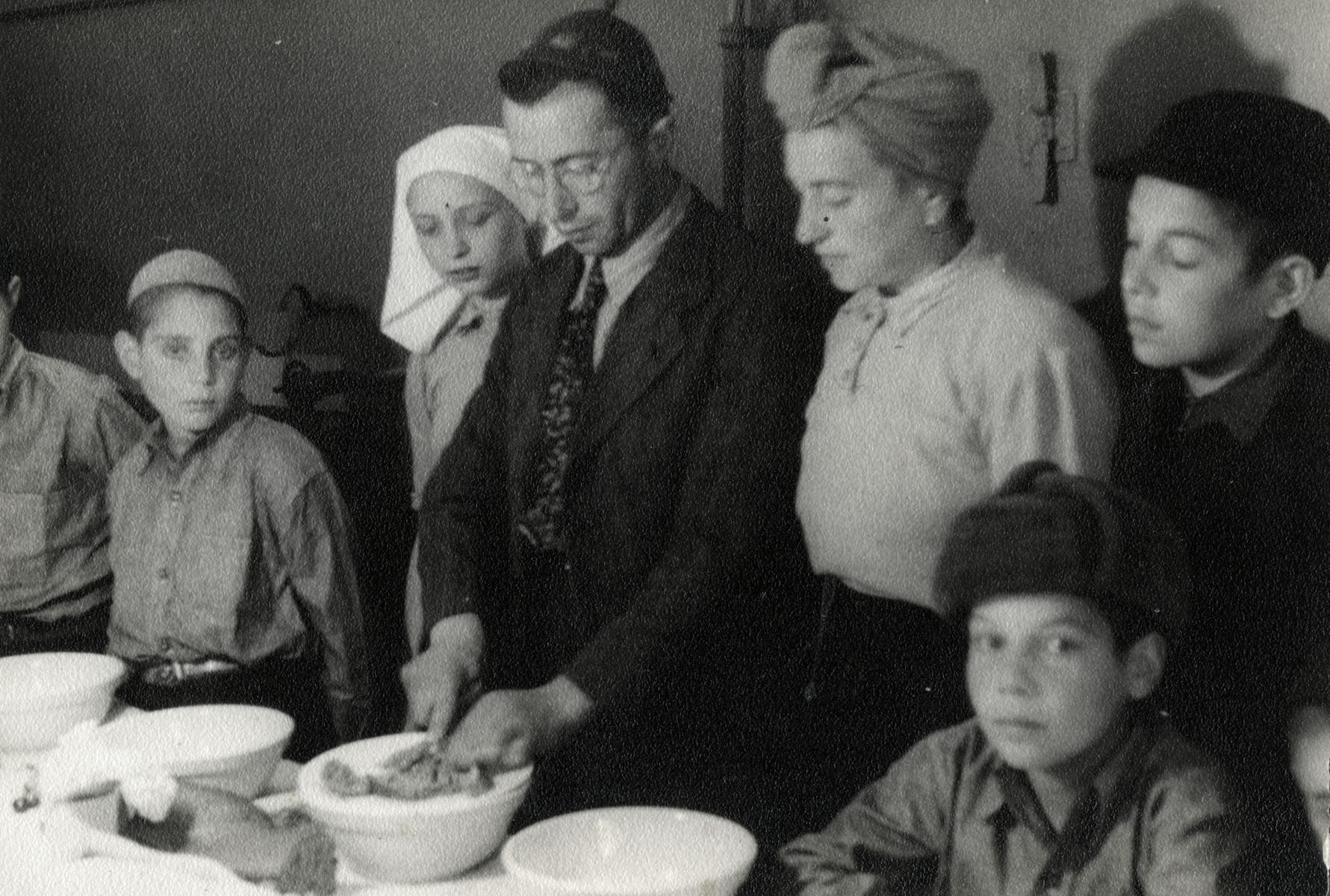 Yehoshua Birnbaum prepares a meal in a home in Maastricht where the family was staying together with the orphans under their care.  From left to right are Walter Kugler, Sonni, Yehoshua and Hennie Birnbaum and Paul Oppenheimer (in the black fur hat).