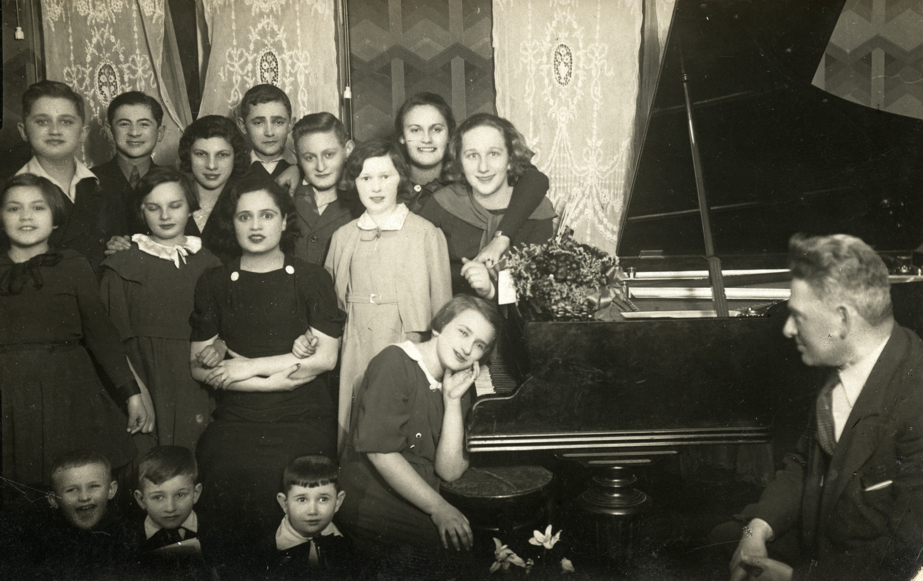 Group portrait of piano students and their teacher.  Ewa Kracowska is standing next to the piano, wearing a light-colored dress. Her teacher, Fanya Kaplan, is standing on the far right. Julia Kracowska is in front, and Genya Lipkis is standing on the far left.
