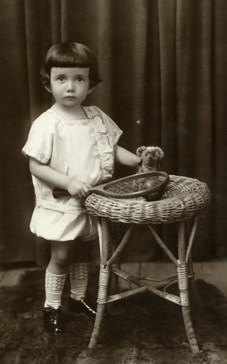 A studio portrait of two-year-old Julek  Kracowski with a tennis racket and teddy bear.