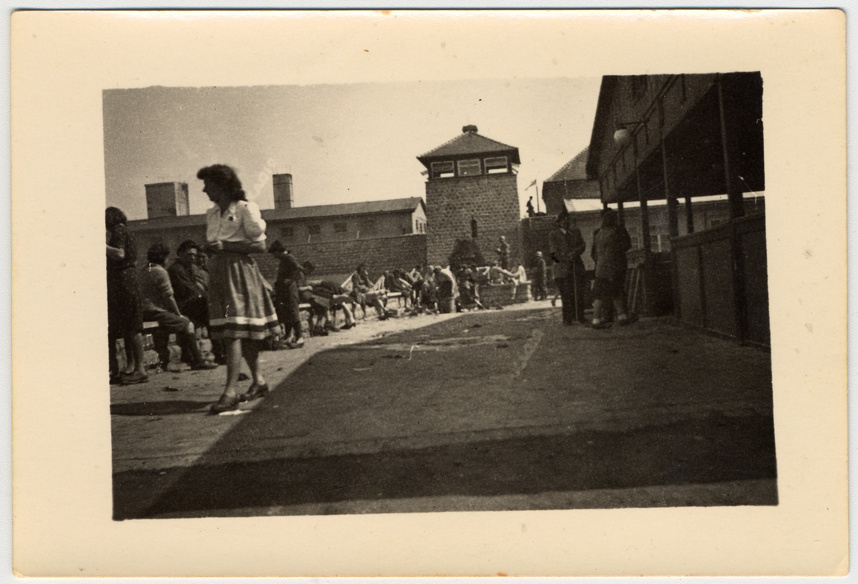 A woman [probably an Austrian civilian] walks past survivors in the Mauthausen concentration camp.