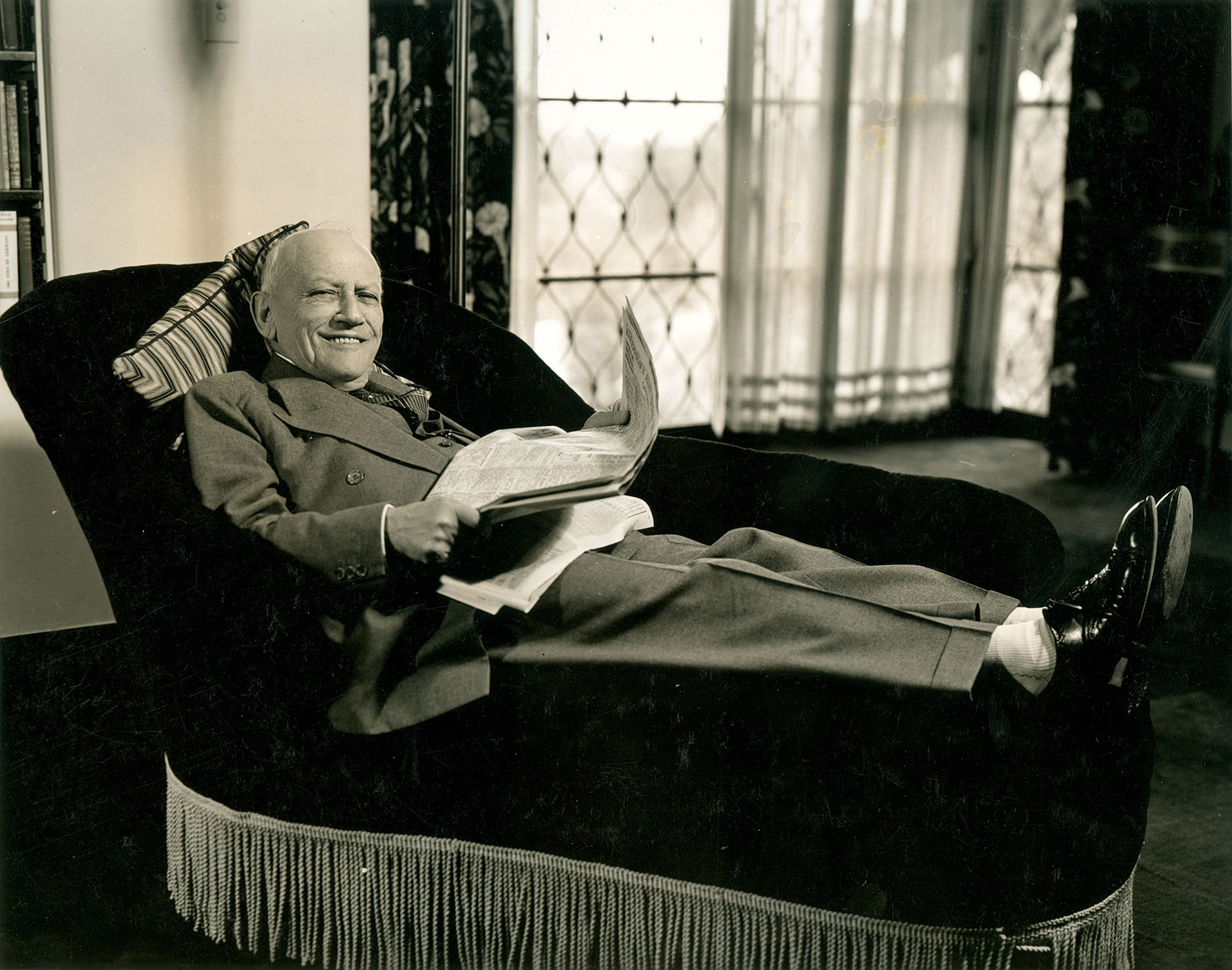 Hollywood producer Carl Laemmle rests on a couch reading a newspaper.