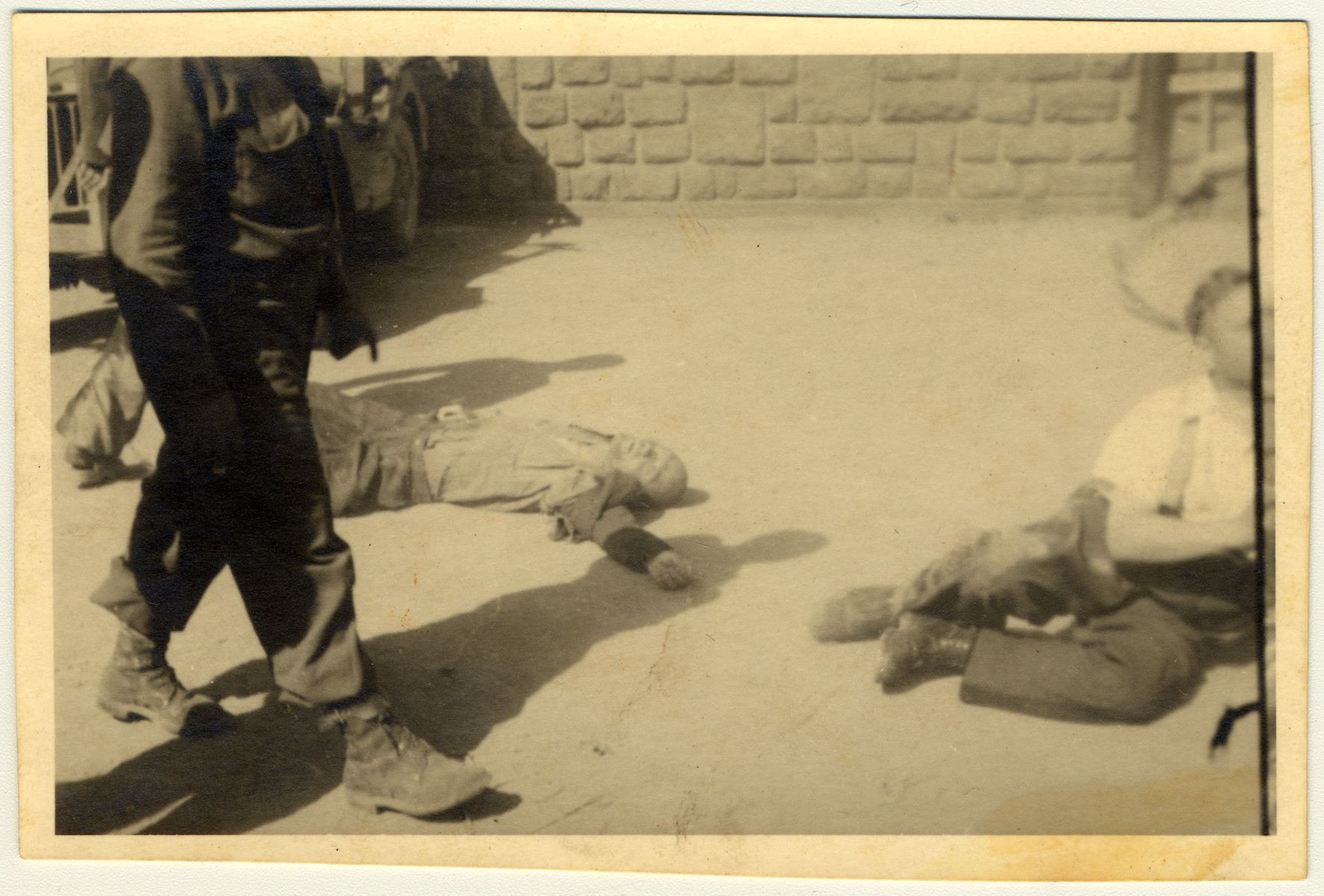 A man walks past the body of an SS guard in the Mauthuasen concentration camp following liberation.