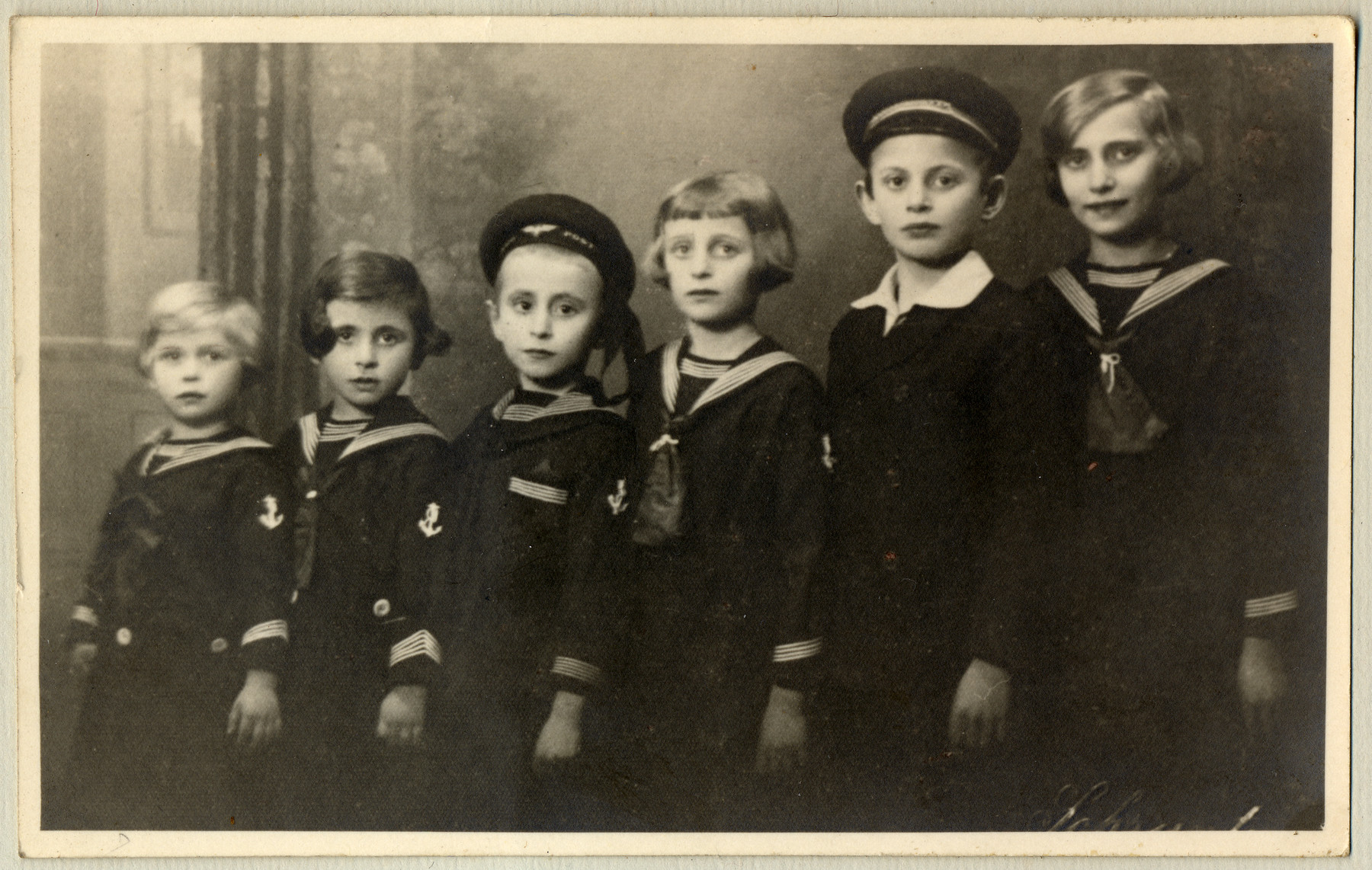 Studio portrait of the Kuttner children, dressed in matching sailor suits.  From left to right are Edit, Rose, Marcel, Sara, Jozsef and Gyongyi Kuttner.