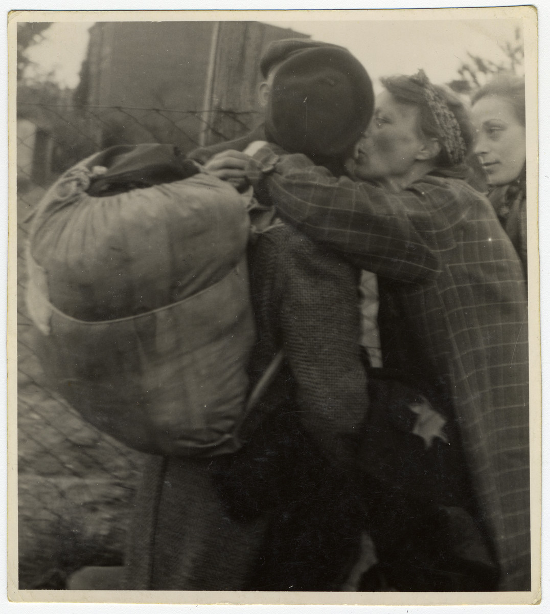 A woman kisses another goodbye next to a fence during Gehsperre action in Lodz ghetto.