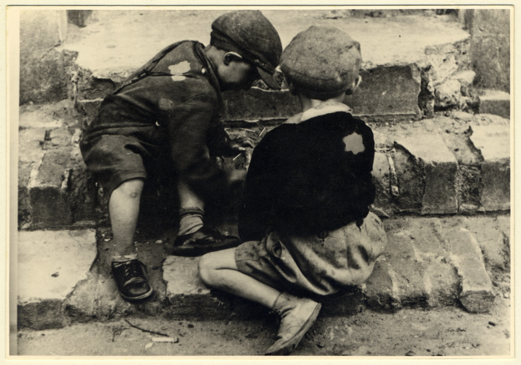 Two children of the Lodz ghetto play on the doorstep of a house.
