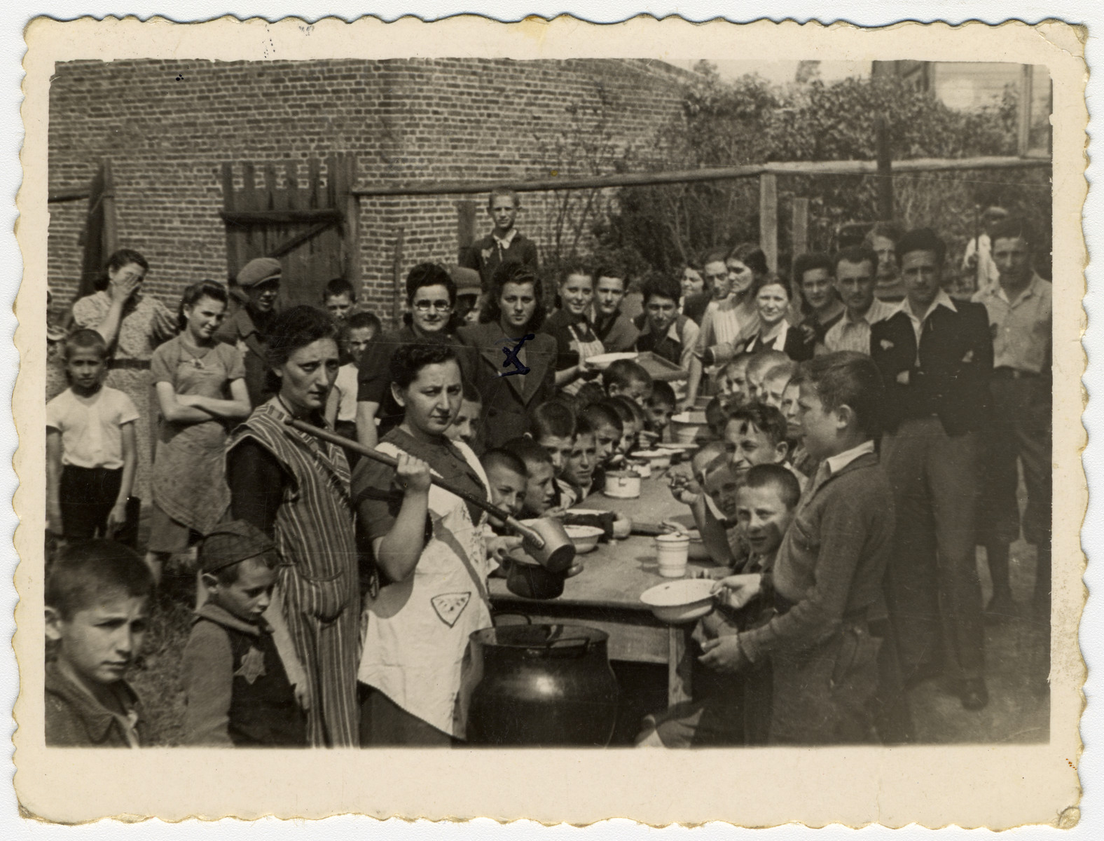 Children in an orphanage in Marysin sit around an outdoor table awaiting the distribution of soup.   In the middle, dividing the food, is the director of the children's home, Mrs. Litman.
