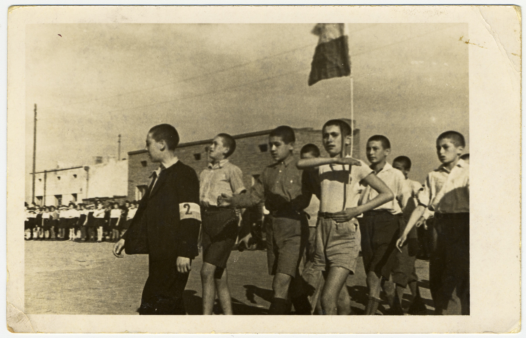Young teenage boys, in the Marysin colony, parade with a flag, in front of Rumkowski.