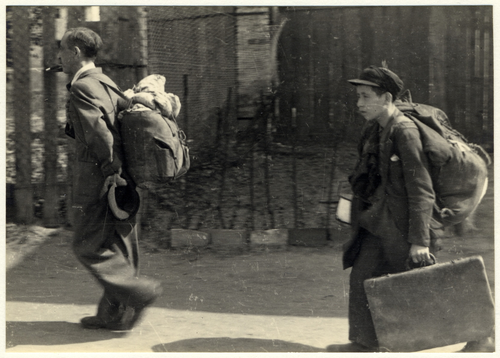 A man and a boy carry their luggage on the way to the deportation train in the Lodz ghetto.