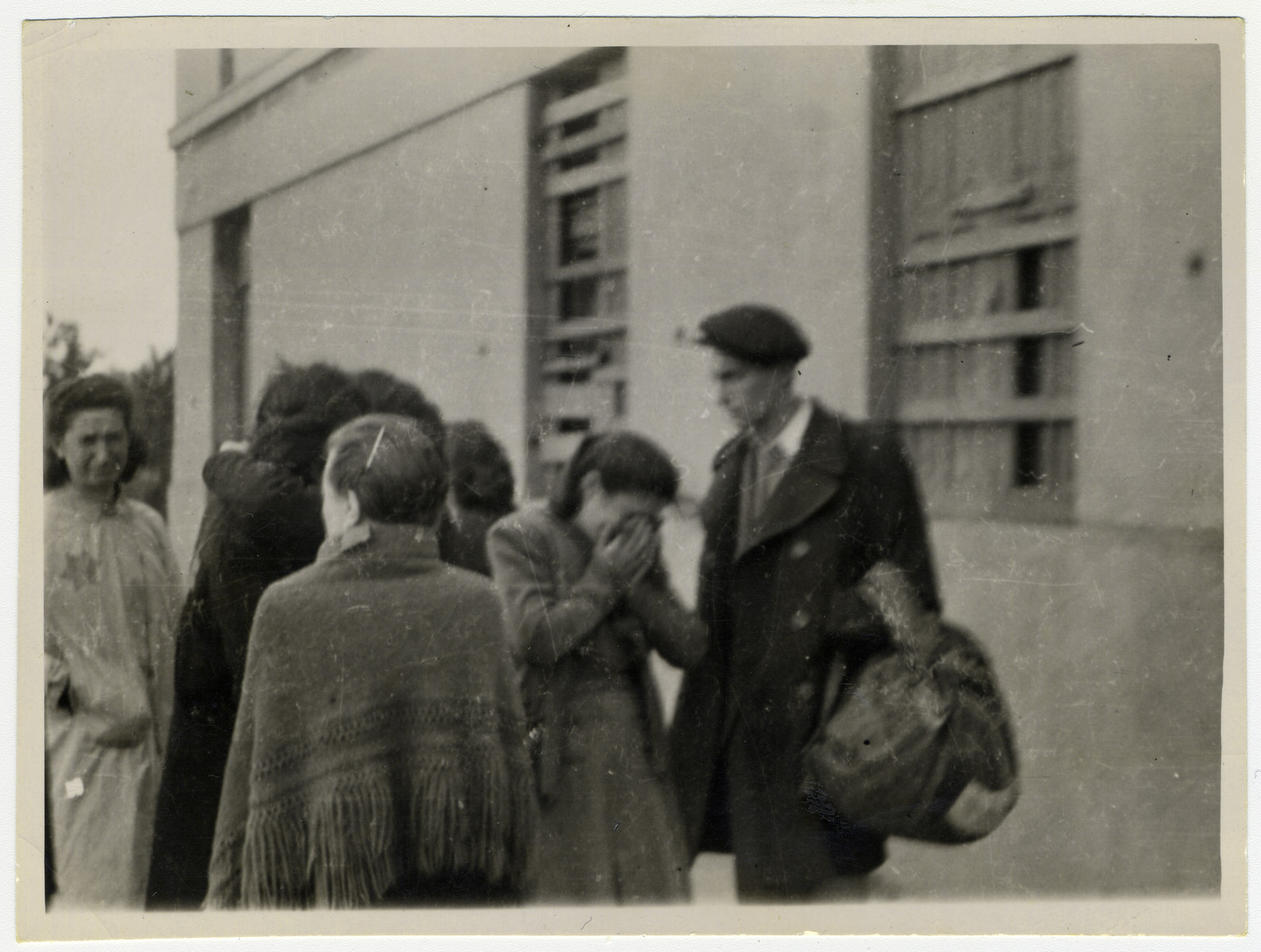 "Sixteen-year-old Pola Znamirowska weeps outside the central prison in the Lodz ghetto during the ""Gehsperre"" action.    She had been separated from her mother and brother during the action and was taken to the assembly center in the central prison, while they were placed in one of the ghetto hospitals."
